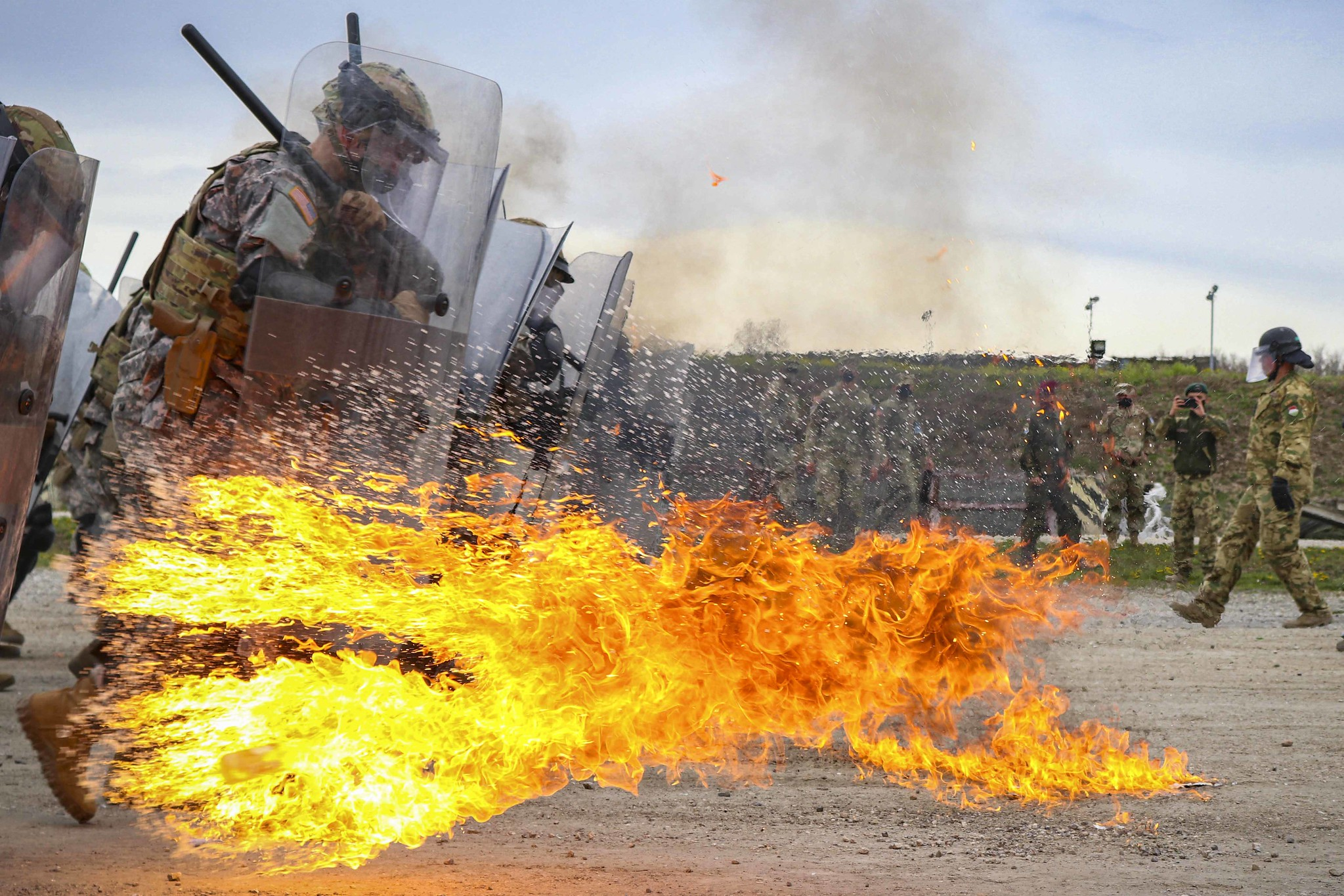 Iowa Army National Guardsmen run through a spray of gasoline and flames during fire phobia training at Camp Novo Selo, Kosovo, April 13, 2021. (Staff Sgt. Tawny Schmit/U.S. Army)