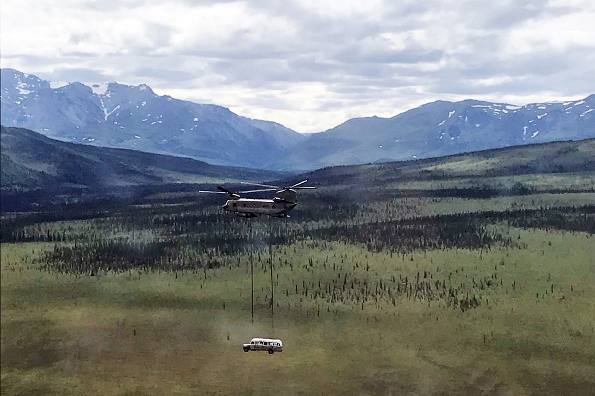 In this photo released by the Alaska National Guard, Alaska Army National Guard soldiers use a CH-47 Chinook helicopter to airlift an abandoned bus, popularized by the book and movie