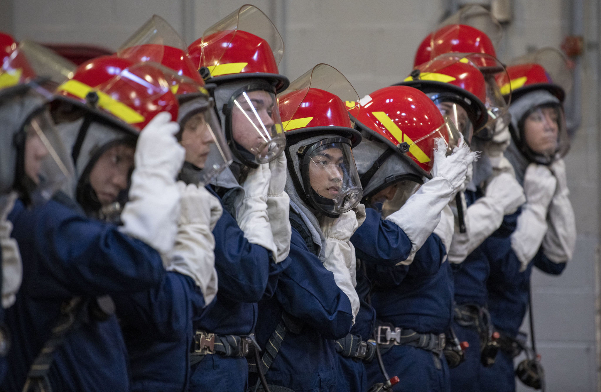 Recruits secure their head gear during firefighting training inside the USS Chief Firefighter Trainer at Recruit Training Command on Jan. 12, 2021, at Great Lakes, Ill. (Seaman Maurice Brown/Navy)