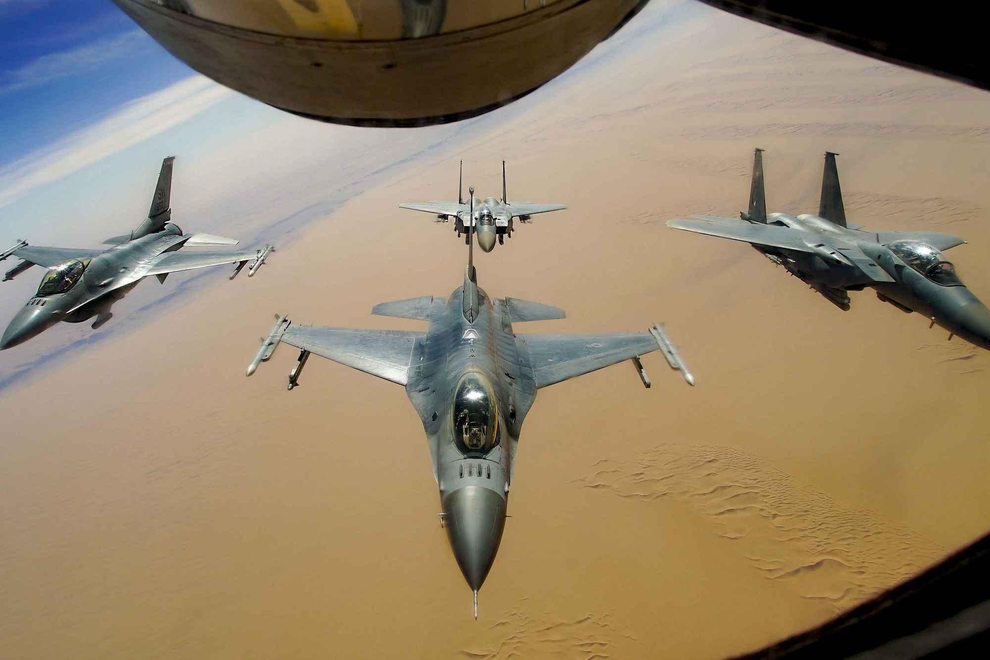 Two U.S. Air Force F-16 Fighting Falcons fly in formation with two Royal Saudi Air Force F-15E Strike Eagles after receiving fuel from a KC-135R Stratotanker during a routine exercise over Southwest Asia, Dec. 15, 2020. (Staff Sgt. Taylor Harrison/Air Force)