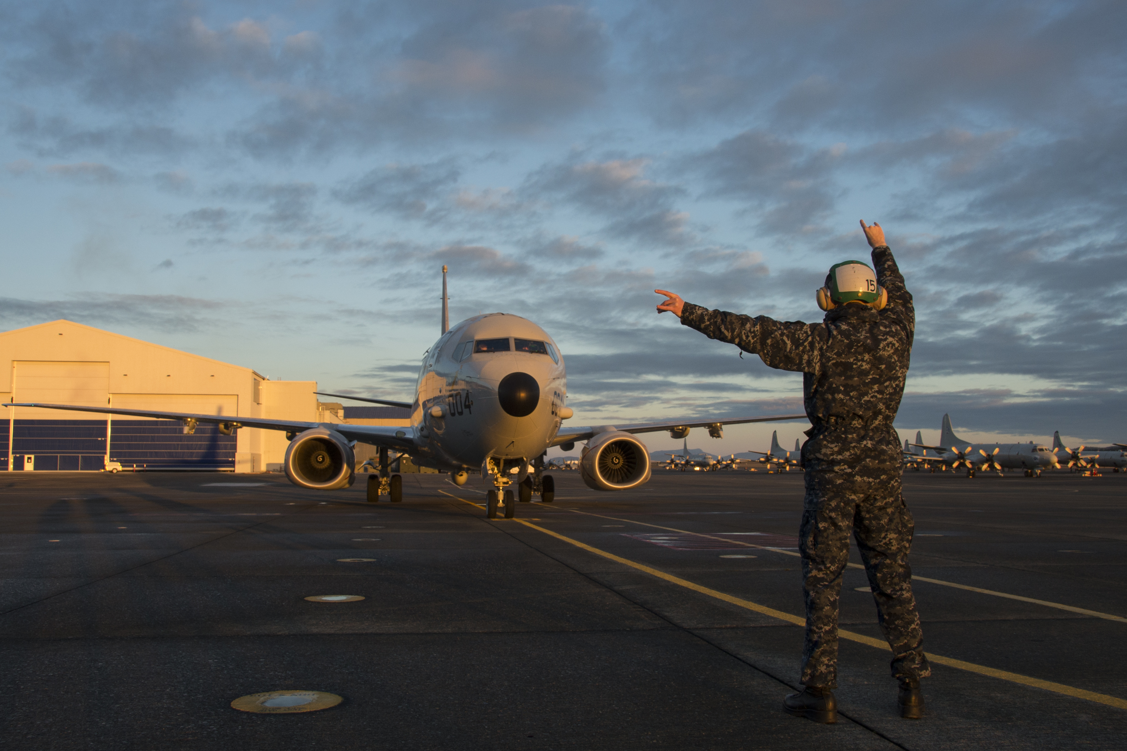 A U.S. Navy sailor directs a P-8 Poseidon flight on Naval Air Station Whidbey Island's Ault Field in 2020. (Petty Officer 3rd Class Juan Sua/U.S. Navy)