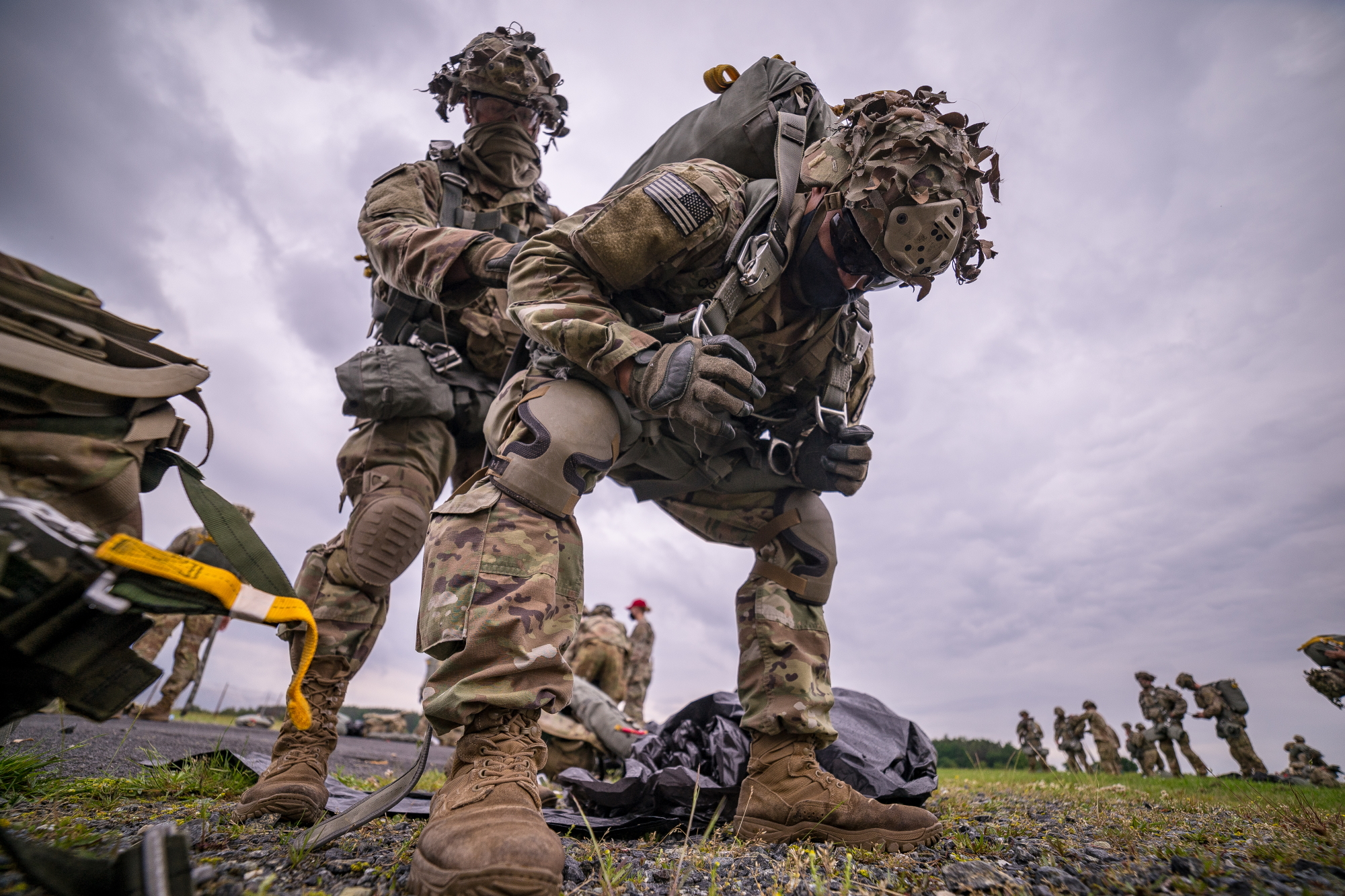 U.S. Army paratroopers from the 1st Squadron (Airborne), 91st Cavalry Regiment, 173rd Airborne Brigade, help each other don parachutes in preparation for an airborne jump at Grafenwoehr Army Air Field, Germany, June 10, 2020. (Staff Sgt. Christopher Stewart/Army)