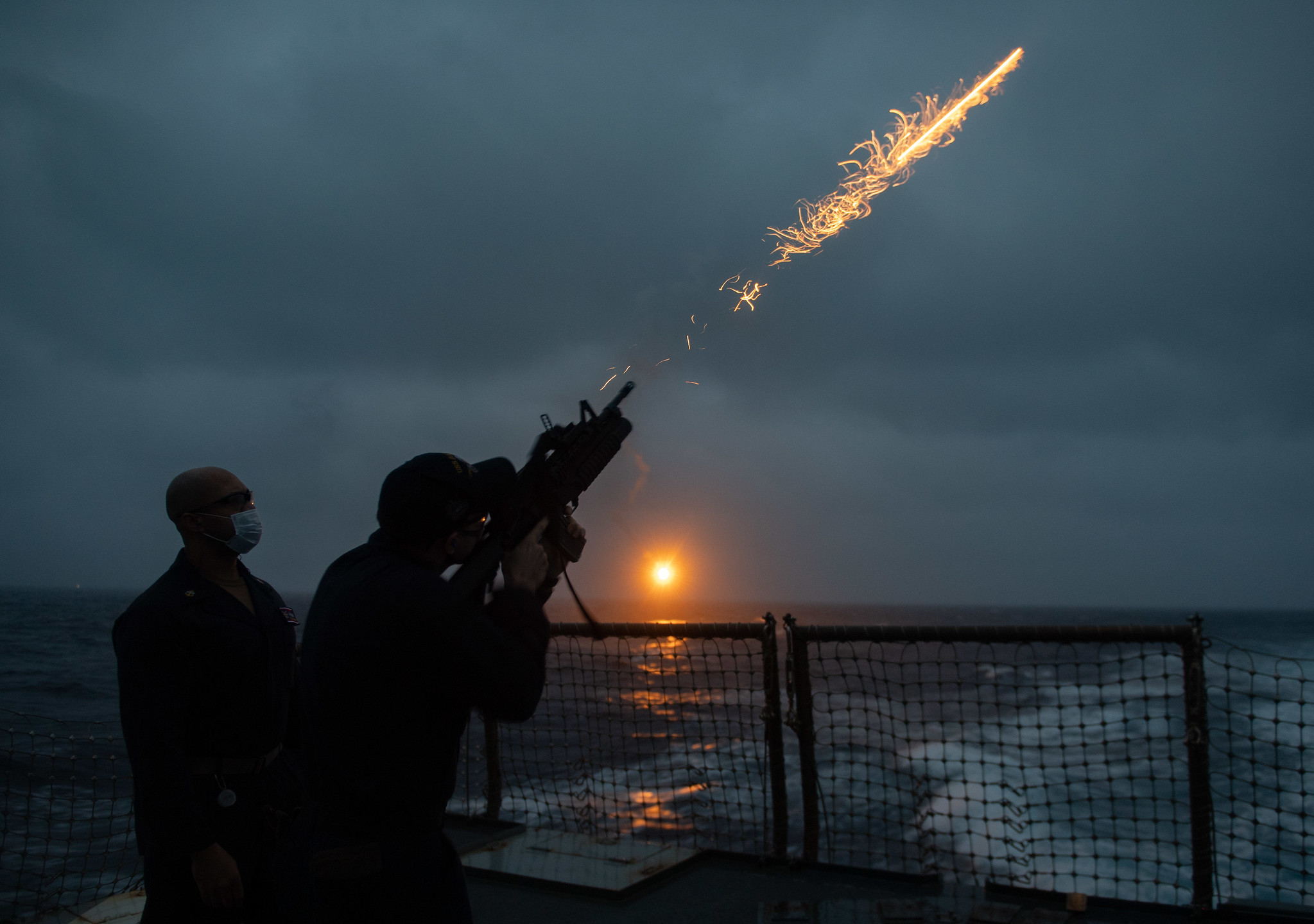 Chief Gunner's Mate Ricardo Stewart, left, watches as Gunner's Mate 3rd Class Cullen McArdle fires a flare during a flare exercise in the Philippine Sea aboard the Arleigh Burke-class guided-missile destroyer USS Barry (DDG 52). (Mass Communications Specialist Seaman Molly M. Crawford/Navy)