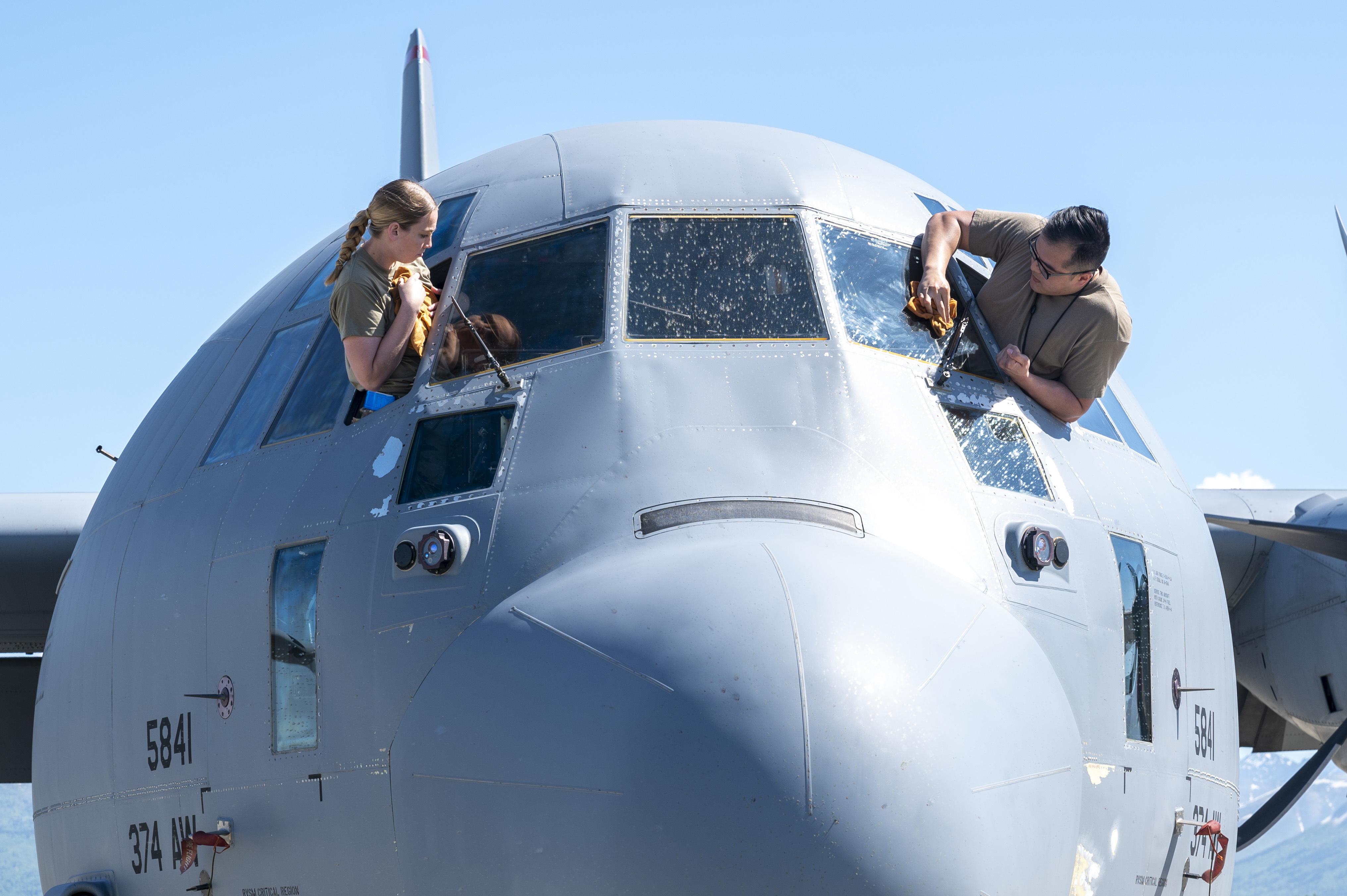Airman 1st Class Sarah Miller and Senior Airman Austin Dihn, 374th Aircraft Maintenance Squadron, clean the windows of a C-130J Super Hercules during Red Flag-Alaska 21-2 at Joint Base Elmendorf-Richardson, Alaska, June 14. (Airman 1st Class Mario Calabro/Air Force)