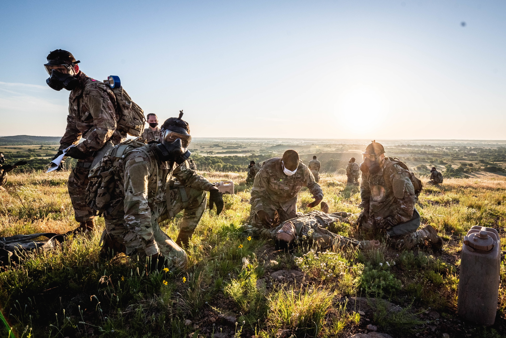 Soldiers treat a mock casualty during a physical training session at Medicine Bluffs on Fort Sill, Okla., May 29, 2020. All soldiers had to wear a face covering to abide by COVID-19 guidance and to ask a challenging element to the session. (Sgt. Amanda Hunt/Army)