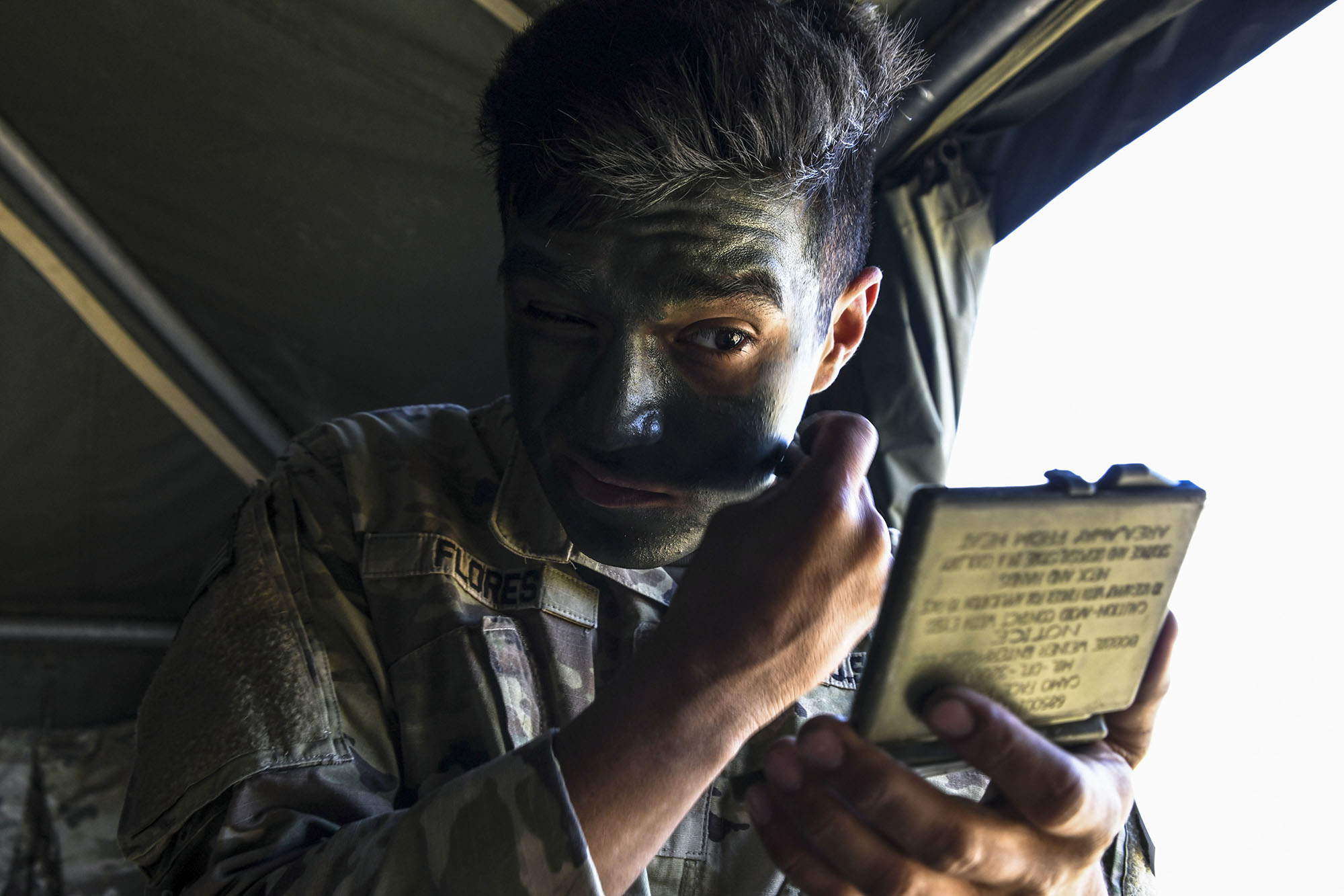 Army Spc. Christian Flores applies face paint prior to mission during the U.S. Army Europe European Best Warrior Competition at U.S. Army Garrison Hohenfels Training Area, Germany, July 29, 2020. (Spc. Austin Riel/Army)