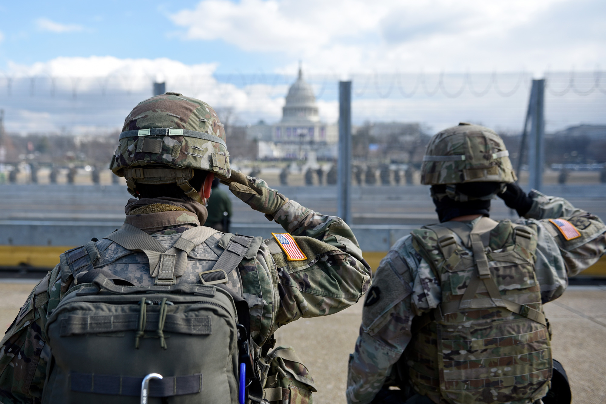 Members of the National Guard salute as they stand near the U.S. Capitol while the national anthem is sung during the inauguration of President-elect Joe Biden and Vice President-elect Kamala Harris on Jan. 20, 2021, in Washington. (Stephanie Keith/Getty Images)