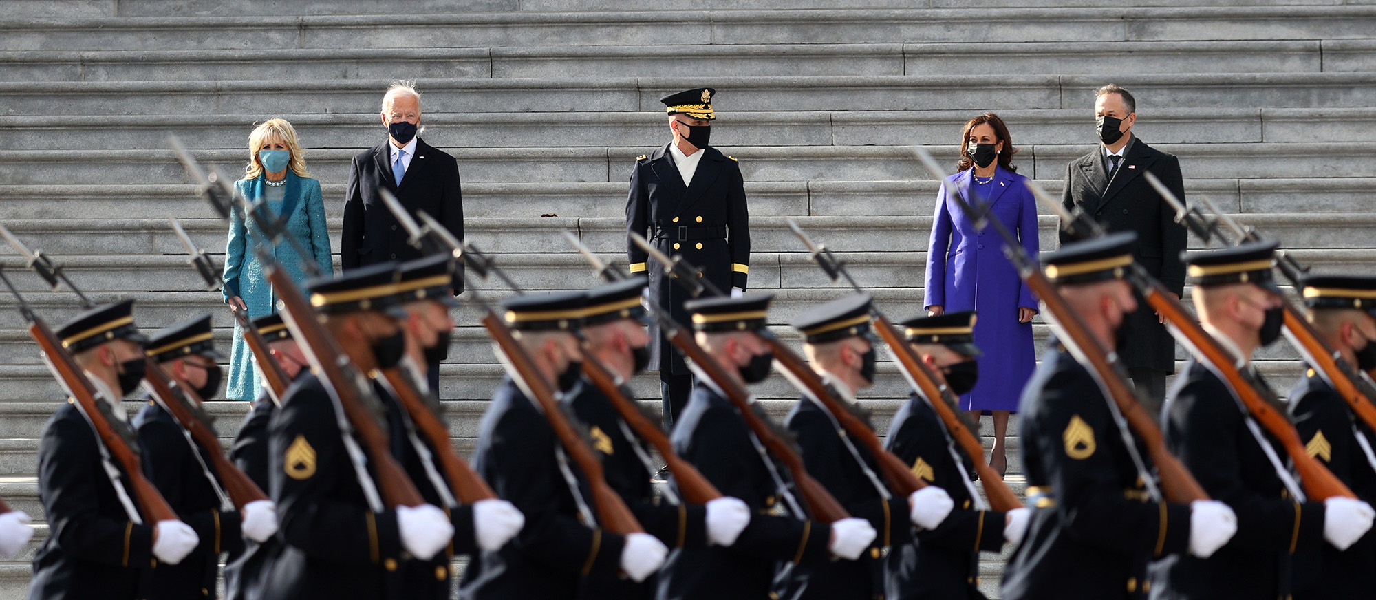 From left to right: first lady Dr. Jill Biden, President Joe Biden, Vice President Kamala Harris, and Doug Emhoffl, Harris' husband, watch a military pass-in-review during the inauguration on the West Front of the Capitol on January 20, 2021 in Washington. (Joe Raedle/Getty Images)