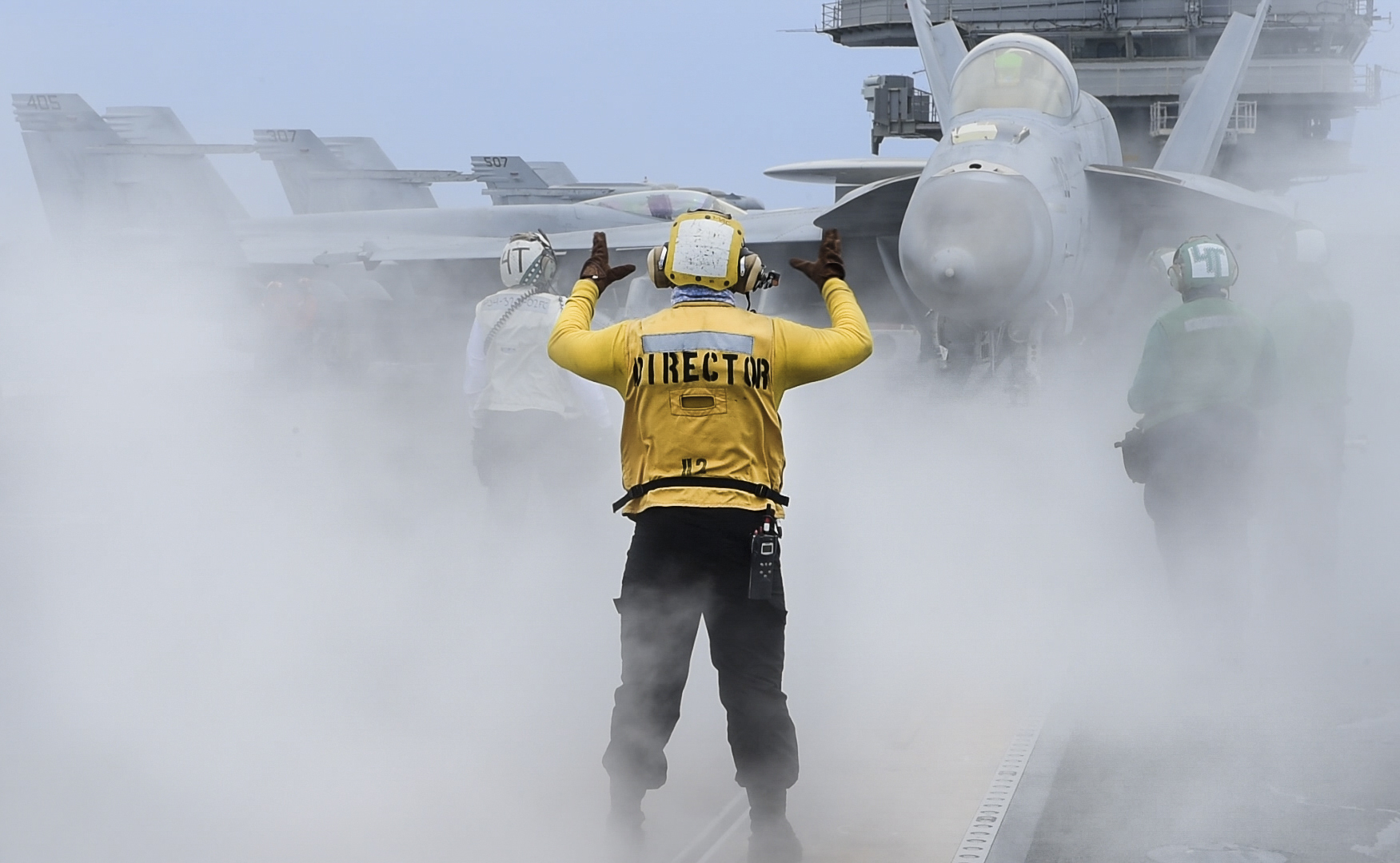 Aviation Boatswain's Mate (Handling) Airman Thomas McLaughlin directs an F/A-18E Super Hornet on May 26, 2020, on the flight deck of the aircraft carrier USS Ronald Reagan (CVN 76) in the Philippine Sea. (MC3 Erica Bechard/Navy)