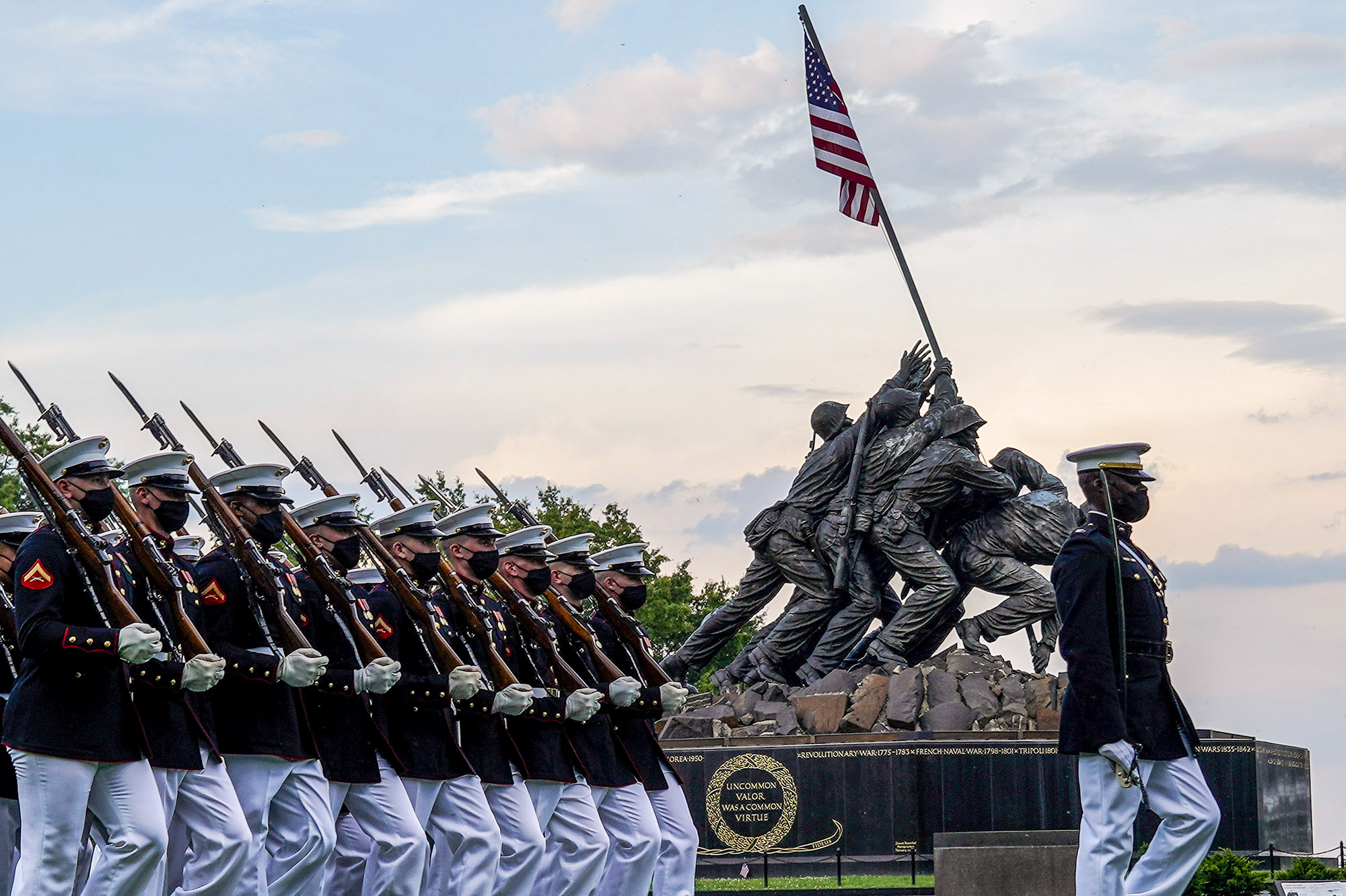 """Marines with the Silent Drill Platoon march for """"Pass in Review"""" during a Tuesday Sunset Parade at the Marine Corps War Memorial, Arlington, Va., June 8, 2021. (Sgt. Jason Kolela/Marine Corps)"""