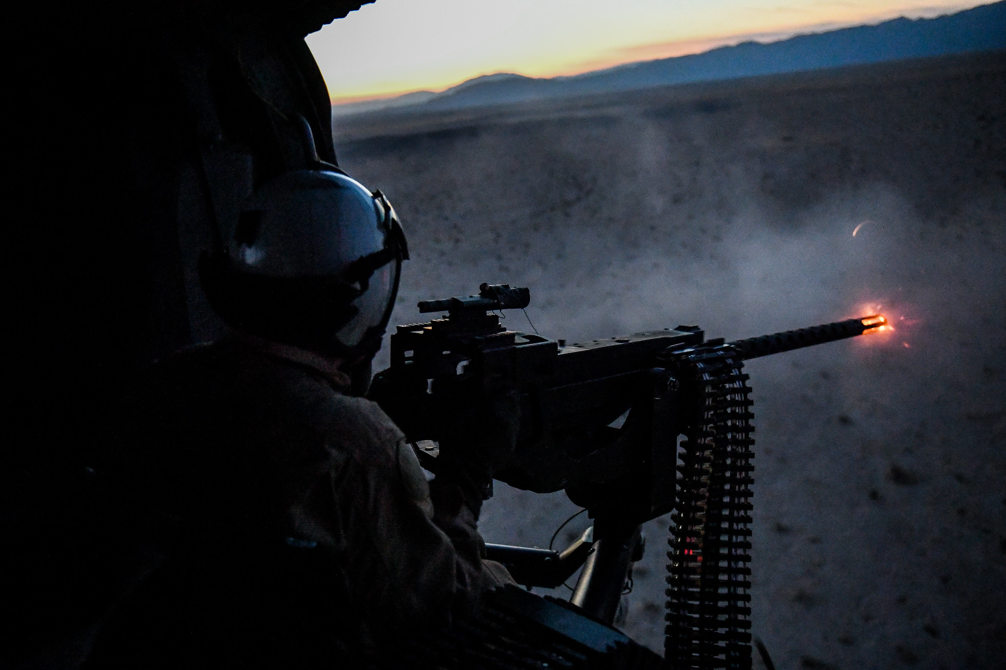 Naval Aircrewman (Helicopter) 3rd Class Copper McCambridge fires a .50-caliber machine gun during an initial aerial gunnery training qualification at Naval Air Facility El Centro, Calif, on Oct. 10, 2020. (Chief Mass Communication Specialist Shannon Renfro/Navy)