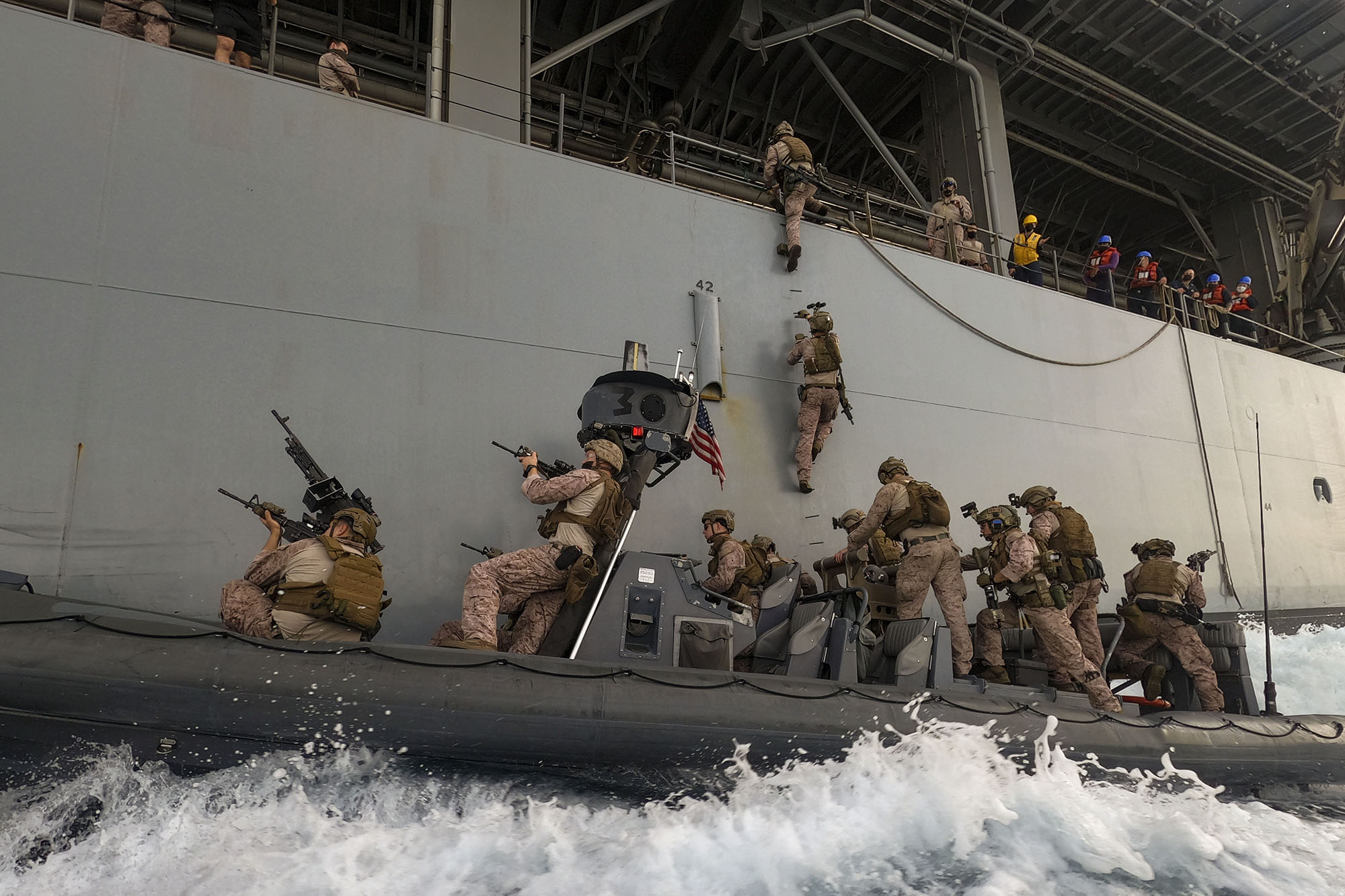 Marines assigned to the All-Domain Reconnaissance Detachment, 15th Marine Expeditionary Unit (MEU), board expeditionary sea base USS Lewis B. Puller (ESB 3) from an 11-meter rigid-hull inflatable boat during visit, board, search and seizure training in the Arabian Gulf, March 19, 2021. (Sgt. Sarah Stegall/Marine Corps)