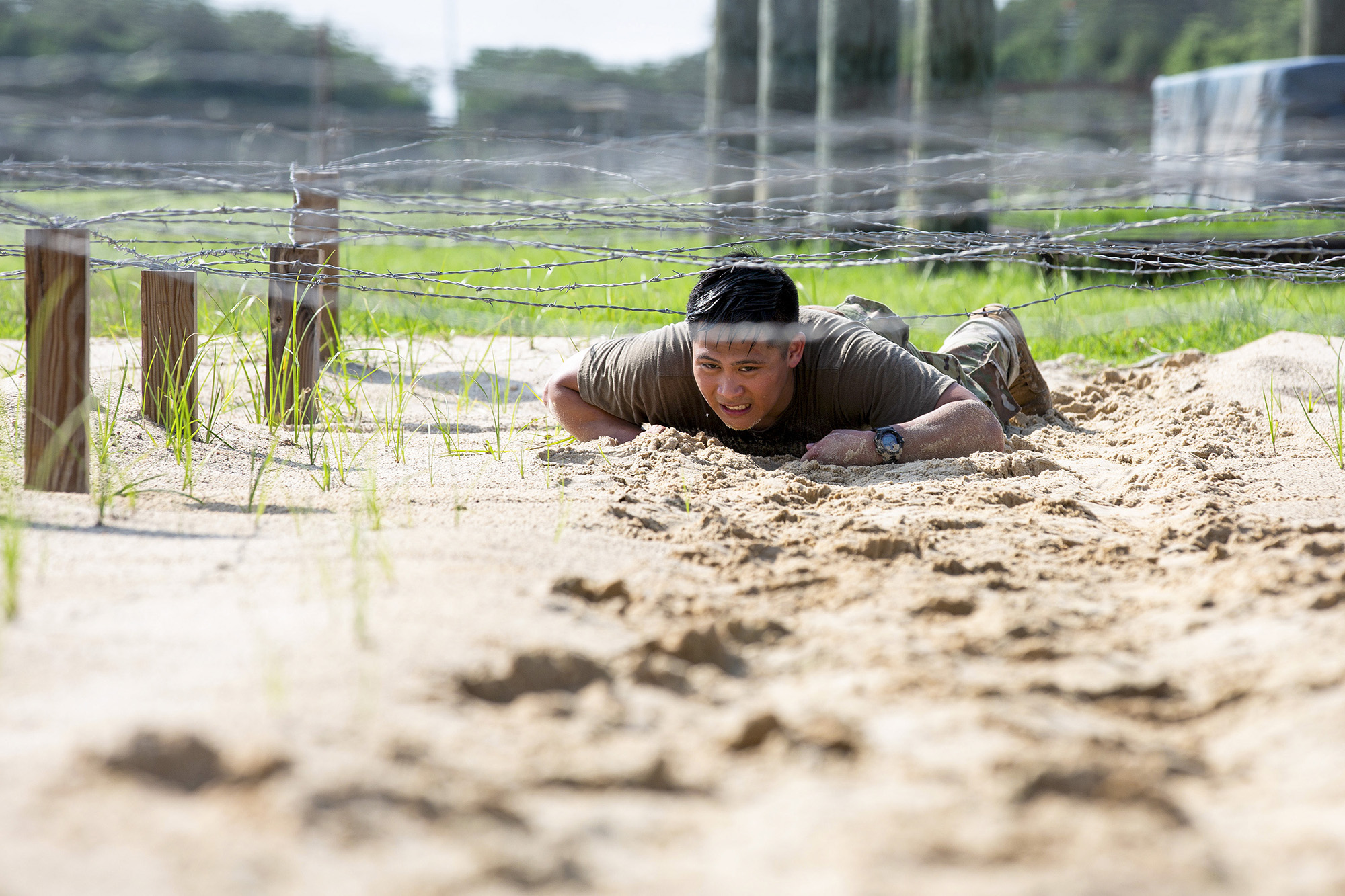 Sgt. Alexander Nguyen, assigned to U.S. Army Future Command, low crawls under barbwire June 8, 2021, during the obstacle course event of the Army Futures Command Best Warrior Competition at Joint Base San Antonio-Fort Sam Houston, Texas. (Spc. Ashlind House/Army)