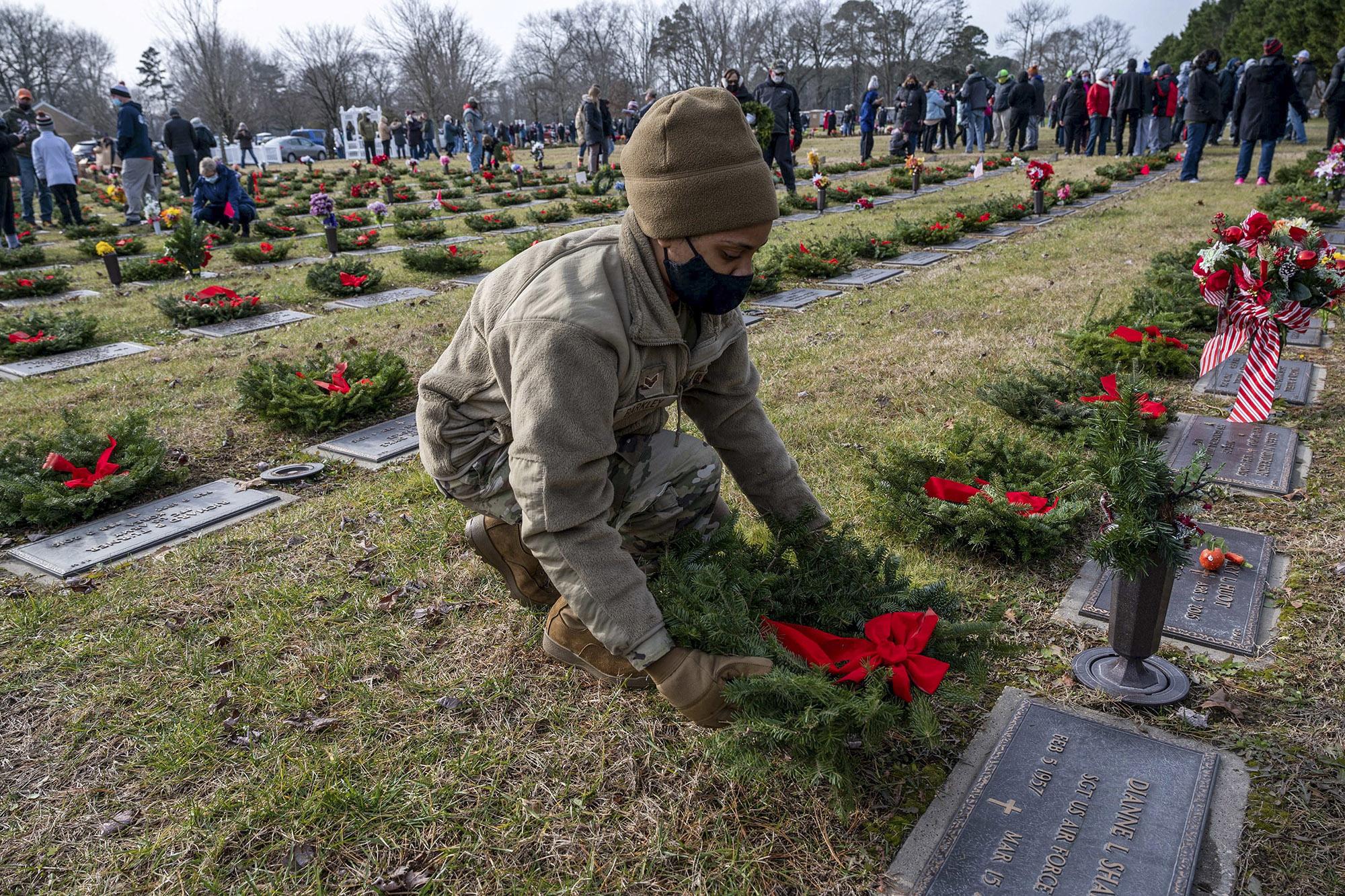 Senior Airman Amber Barkley lays a wreath on a grave at the Delaware Veterans Memorial Cemetery in Millsboro, Del., Dec. 19, 2020. (Airman 1st Class Faith Schaefer/Air Force)