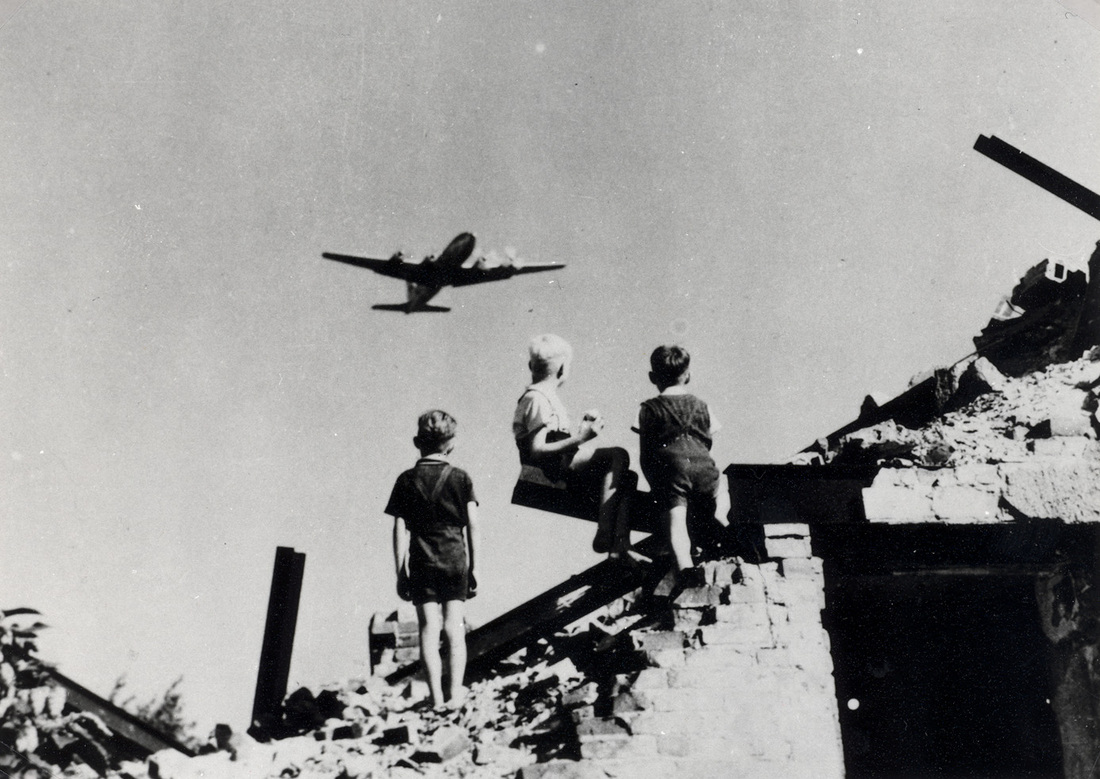 Children look on as a plane flies overhead. In 1948, the U.S. reportedly delivered some 13,000 tons of cargo and took off more than 89,000 times, totaling more than 600,000 hours of flight.
