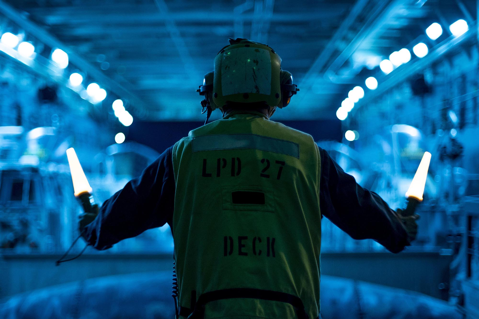 A sailor signals an air-cushioned landing craft to depart the well deck of the USS Portland for an amphibious raid exercise in the Pacific Ocean, May 17, 2021. (Cpl. Ian M. Simmons/Marine Corps)