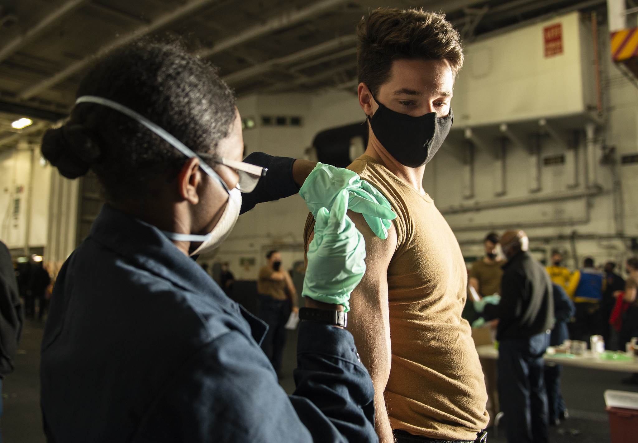 Aviation Ordnanceman Airman Michael Beatty, right, receives an influenza vaccine from Hospitalman Glenda Martinez on Nov. 20, 2020, in the hangar bay of the aircraft carrier USS Carl Vinson (CVN 70) in the Pacific Ocean. (MC2 Ellen E. Sharkey/Navy)