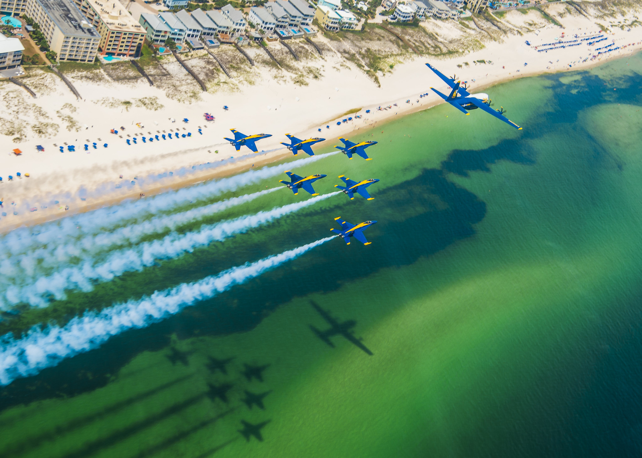 The U.S. Navy Flight Demonstration Squadron, the Blue Angels, C-130 pilots and crew arrive at Naval Air Station Pensacola with the team's new C-130J Super Hercules, alongside the Blue Angel delta formation on Aug. 17, 2020. (MC2 Cody Hendrix/Navy)