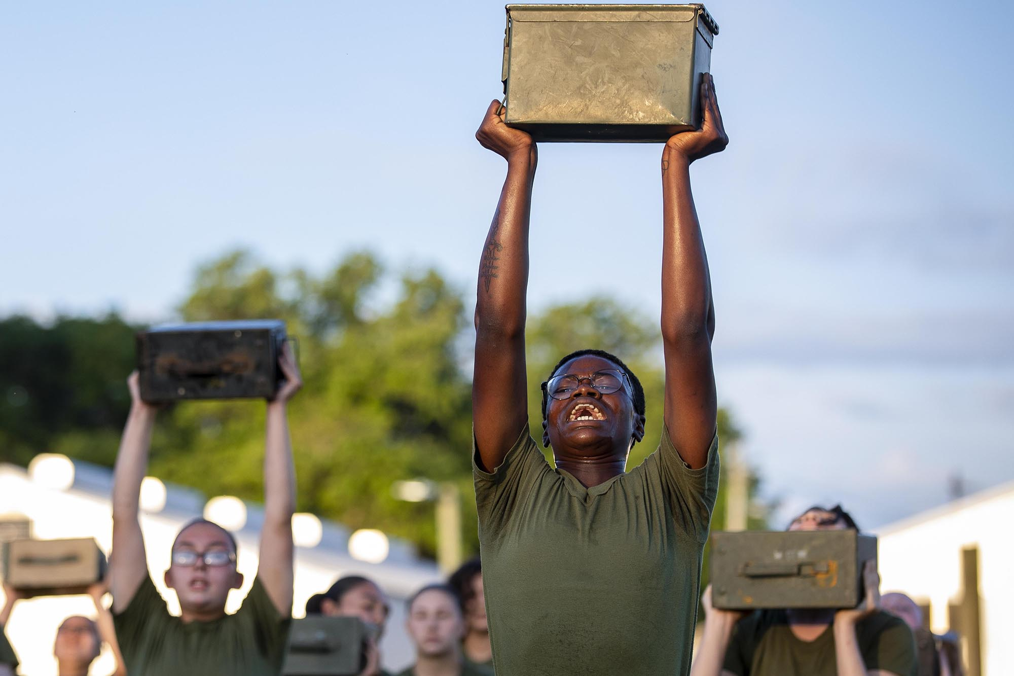 Recruits with Papa Company, 4th Recruit Training Battalion, execute ammo can lifts during physical training on Marine Corps Recruit Depot Parris Island, S.C., May 11, 2021. (Sgt. Dana Beesley/Marine Corps)