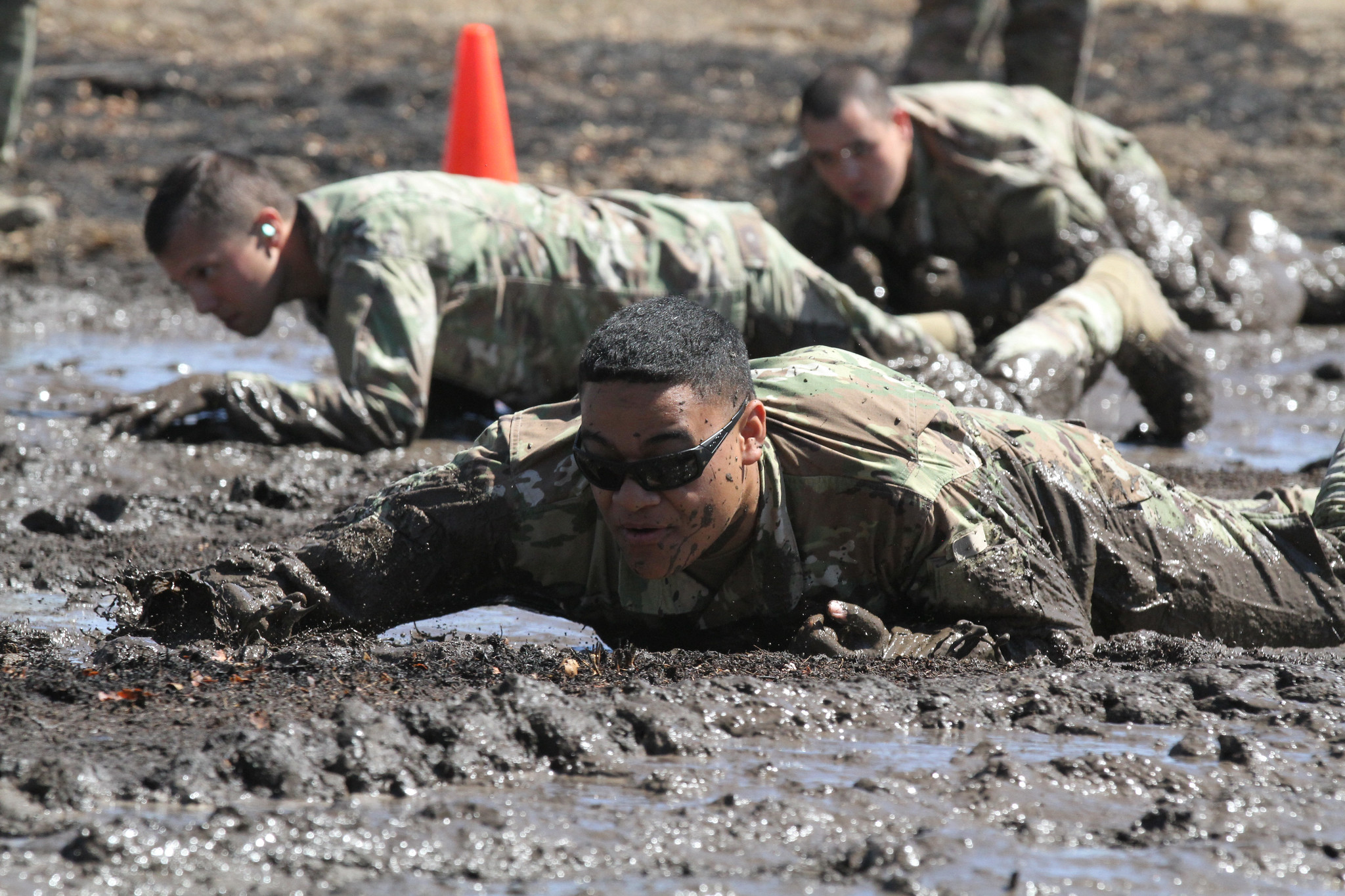 U.S. Army Sgt. Miguel Leyua of the California National Guard's 330th Military Police Company, 143rd Military Police Battalion, 49th Military Police Brigade, one of the cadres of the 49th's 2020 Best Warrior Competition, low crawls through a mud pit during the competition, Aug. 8-12, 2020 at Camp Roberts, Calif. (Staff Sgt. Eddie Siguenza/Army National Guard)