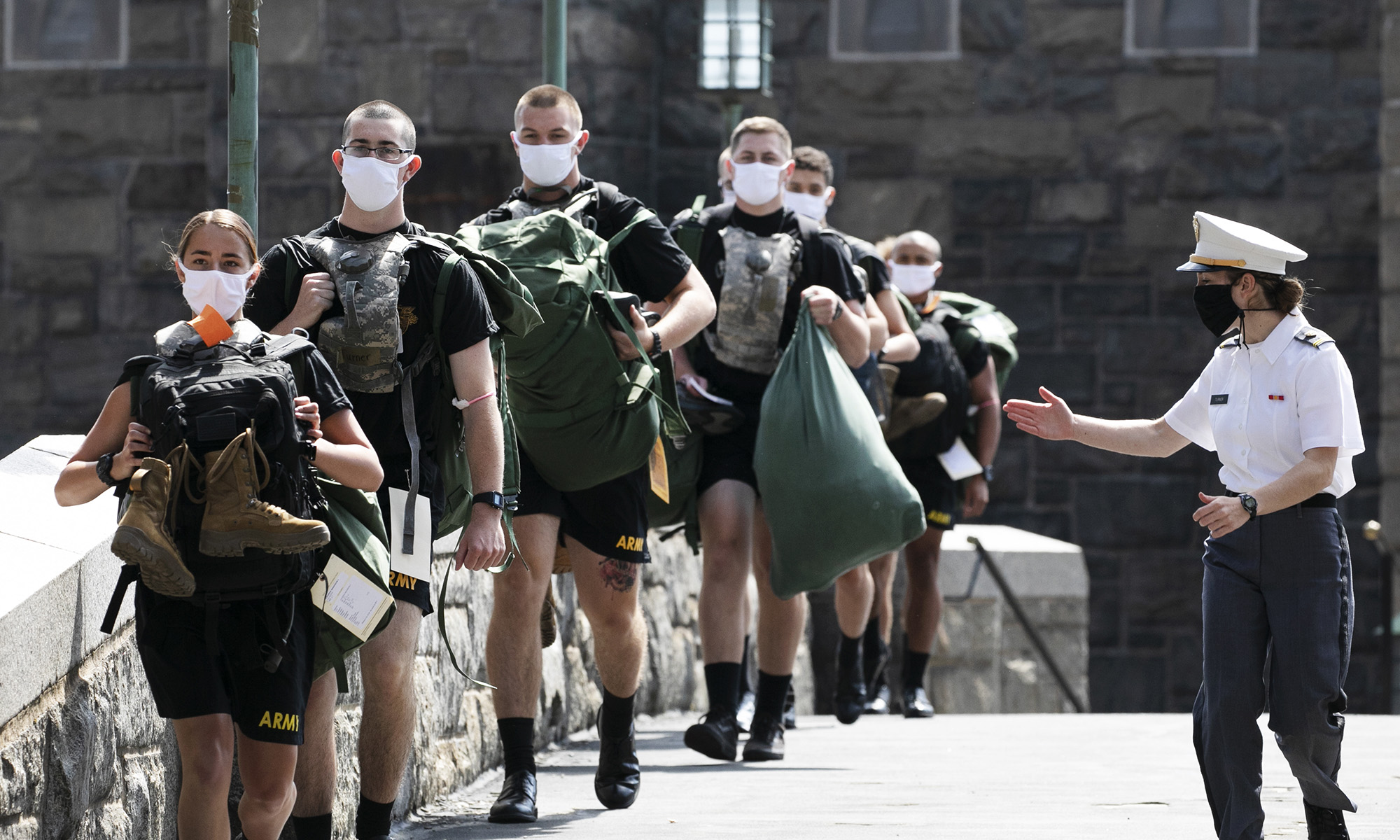 A West Point cadet, right, leads a formation of new cadets on July 13, 2020, at the U.S. Military Academy in West Point, N.Y. The Army is welcoming more than 1,200 candidates from every state. Candidates will be COVID-19 tested immediately upon arrival, wear masks, and practice social distancing. (Mark Lennihan/AP)
