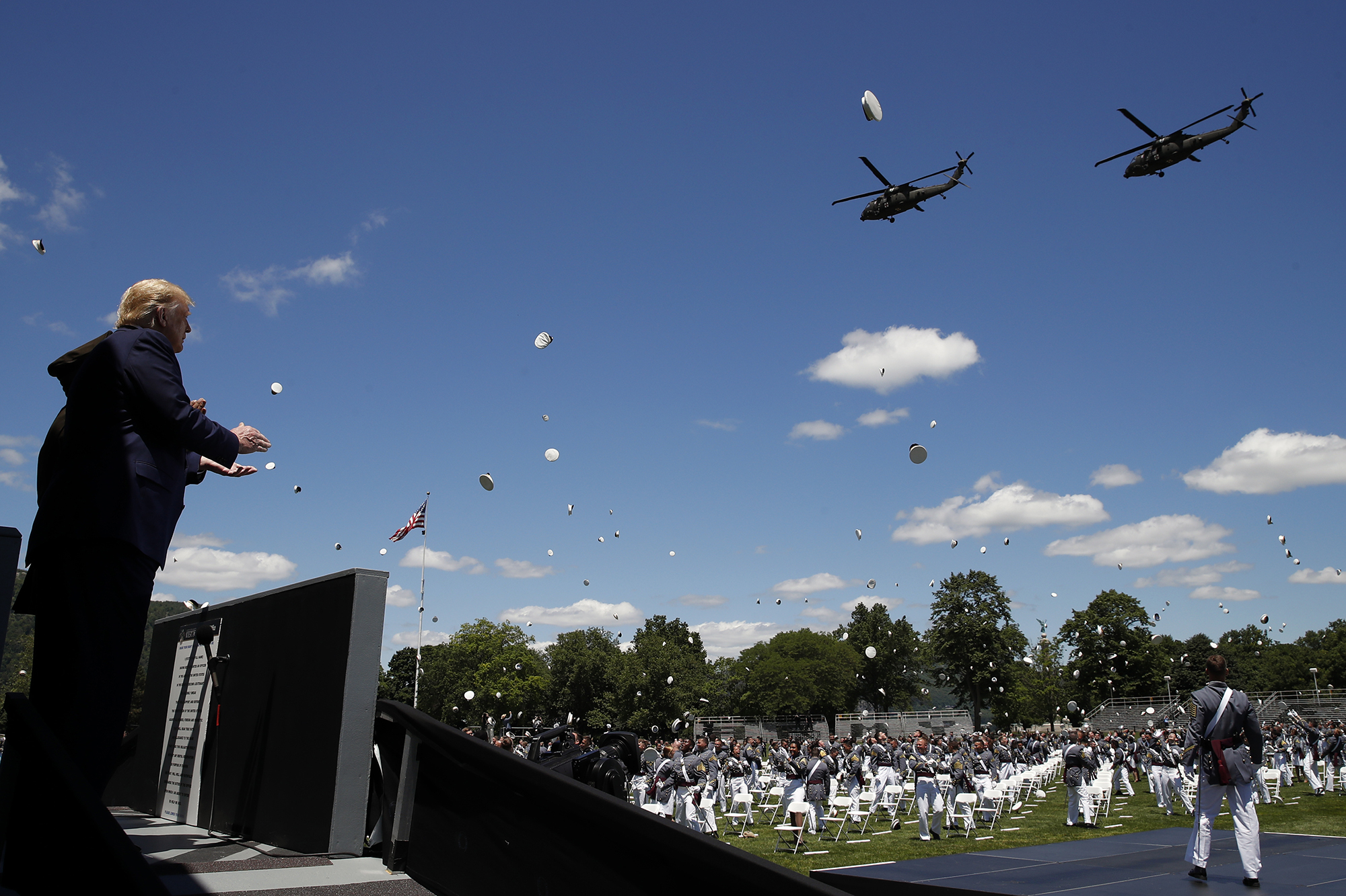 President Donald Trump applauds as Army helicopters fly over and West Point cadets toss their caps into the air at the end of commencement ceremonies on the parade field, at the United States Military Academy in West Point, N.Y., Saturday, June 13, 2020. (Alex Brandon/AP)