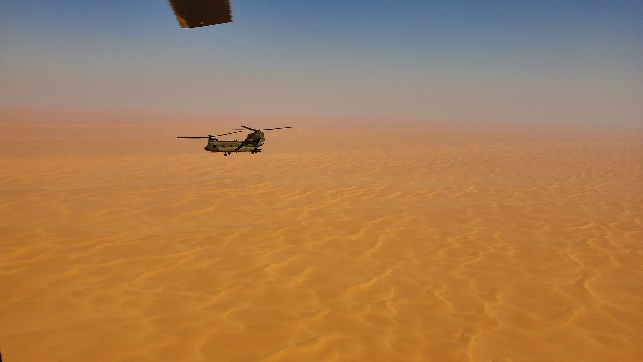 A CH-47 Chinook helicopter, operated by soldiers with Bravo Company, 3-238th General Support Aviation Battalion, 28th Expeditionary Combat Aviation Brigade, flies over a desert on Oct. 18, 2020, in the 28th ECAB's area of operations in the Middle East. (Spc. Jacob Robinson/Army)