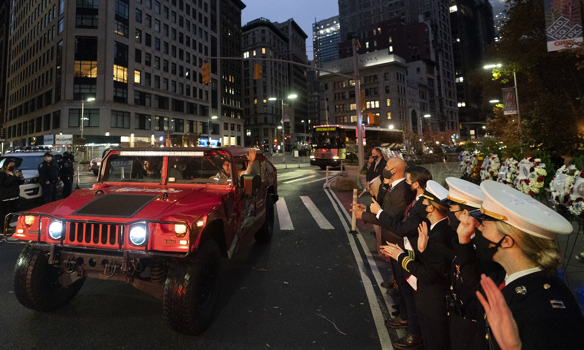 Navy and Marine Corps members watch vehicles pass in a Veterans Day parade, Wednesday, Nov. 11, 2020, in New York. The 100-vehicle parade, with no spectators, was held during the coronavirus pandemic to maintain the 101-year tradition of veterans marching on Fifth Avenue. (Mark Lennihan/AP)