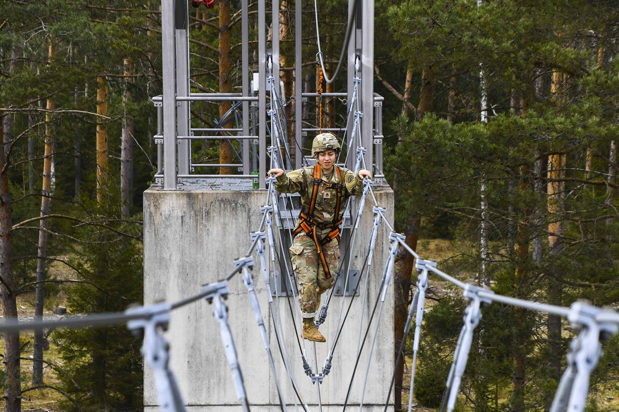 Staff. Sgt. Samantha Delgado crosses a cable bridge during the Army Medical Department Activity Bavaria Best Warrior Competition at the Grafenwoehr Training Area, Germany, April 11, 2021. (Spc. Austin Riel/Army)