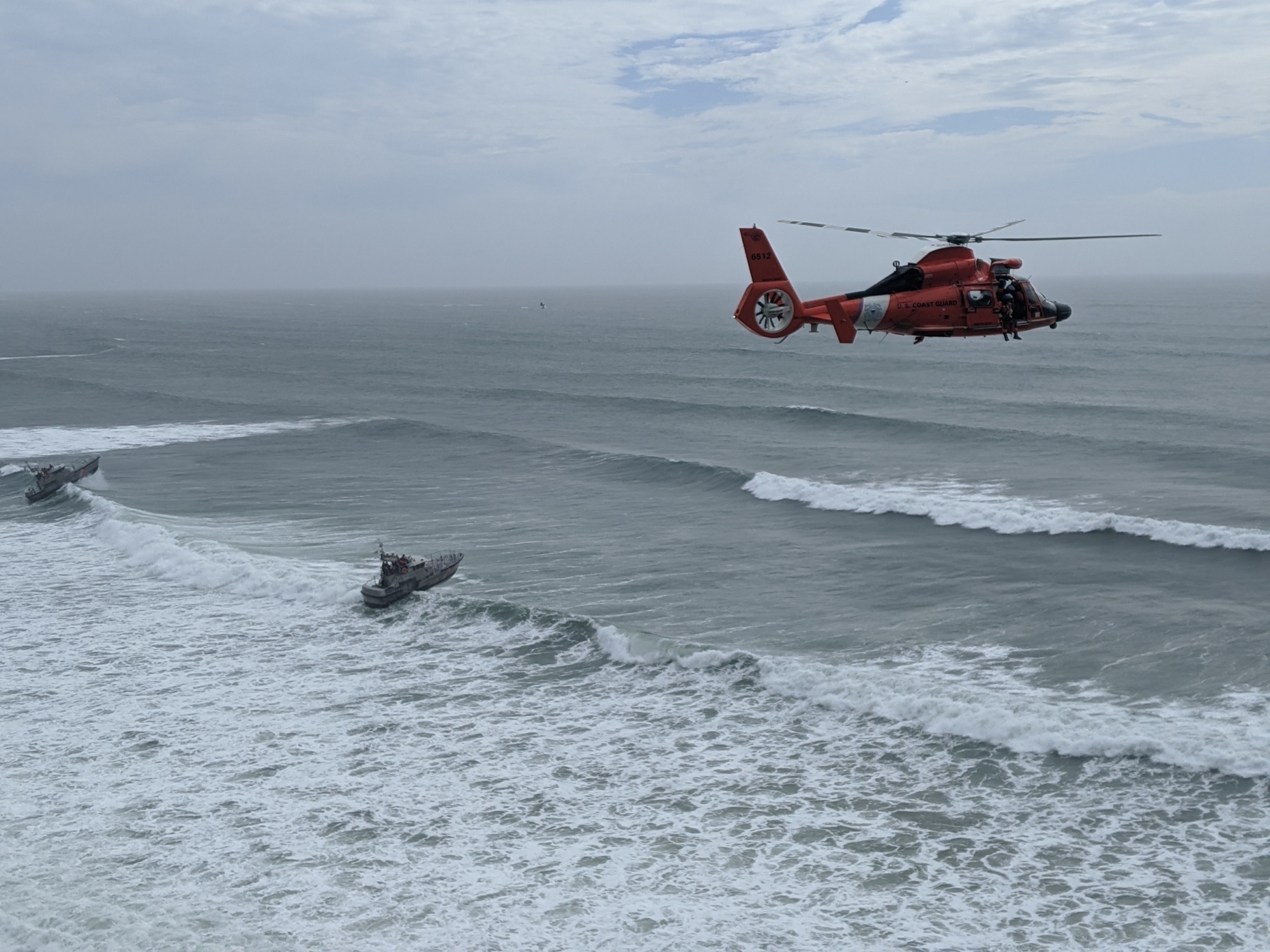 An aircrew aboard an MH-65 Dolphin helicopter from Air Facility Newport arrives on scene during the rescue of seven people trapped on the cliffs near Yaquina Head, Ore., May 29, 2020. Two Station Yaquina Bay boatcrews aboard 47-foot Motor Lifeboats were positioned offshore as a contingency. (Petty Officer 2nd Class Michael Martini/Coast Guard)