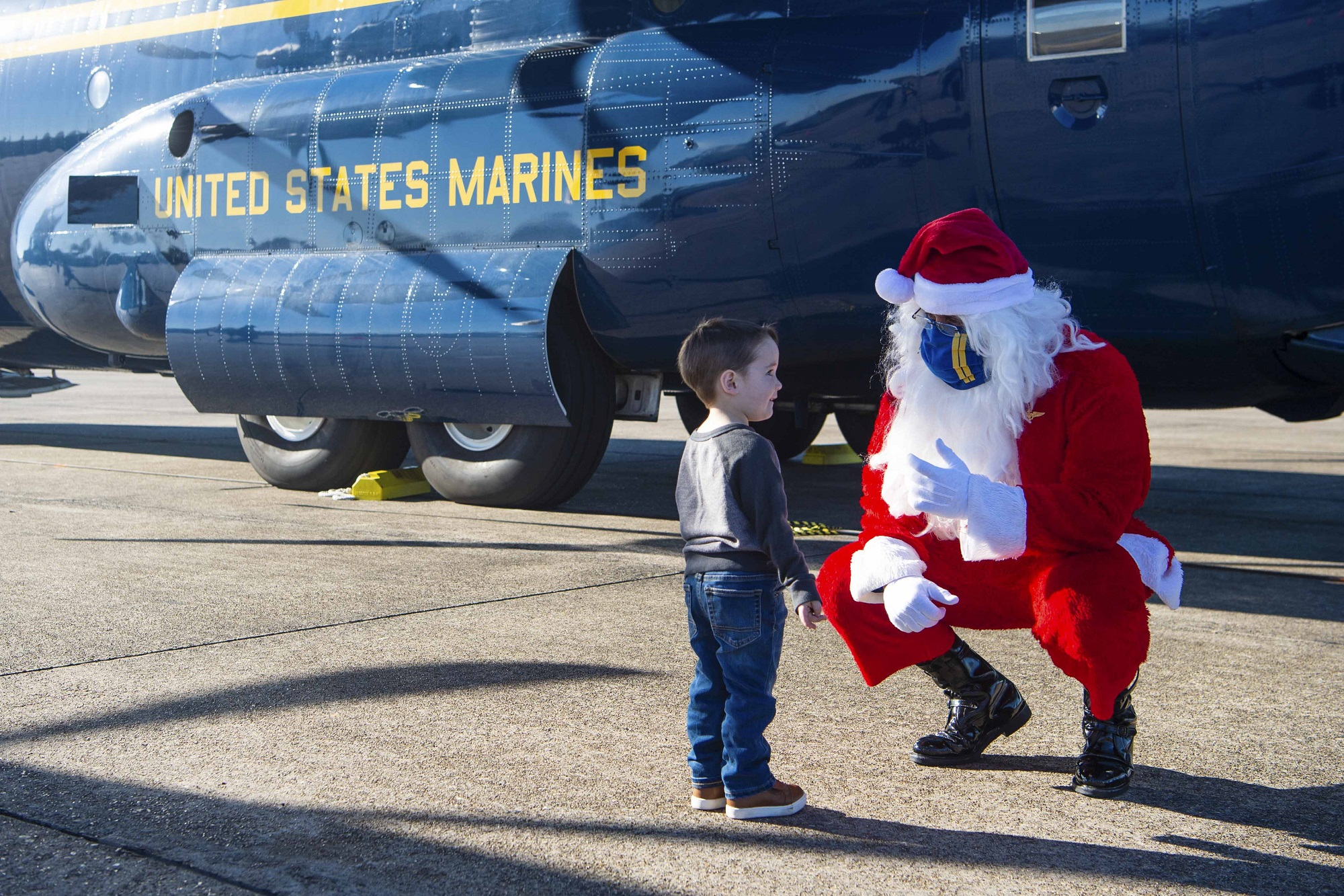 Santa speaks with a child while joining the Blue Angels, the Navy's flight demonstration squadron, to support the Marine Corps Toys for Tots program by delivering toys and games to families impacted by the COVID-19 pandemic and multiple hurricanes in Lake Charles, La., Dec. 8, 2020. (MC2 Cody Hendrix/Navy)
