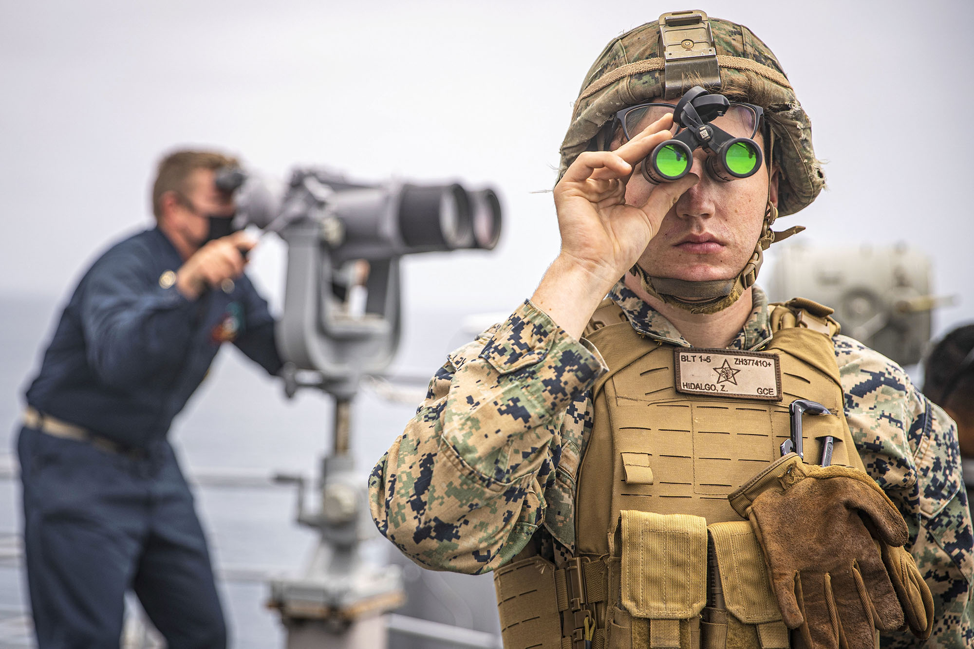 U.S. Marine Corps Lance Cpl. Zachary Hidalgo provides observation during formation April 20, 2021, steaming aboard the amphibious dock landing ship USS Pearl Harbor (LSD 52) in the Pacific Ocean. (Cpl. Jaxson Fryar/Marine Corps)