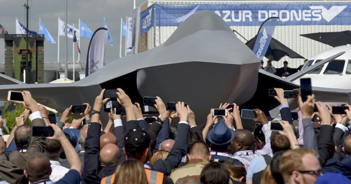 Visitors attend the unveiling ceremony of the full-scale jet fighter model of the Systeme de Combat Aerien Futur (SCAF), the French-German-Spanish new generation Future Combat Air System (FCAS), during the 53rd International Paris Air Show at Le Bourget Airport near Paris, on June 17, 2019. (ERIC PIERMONT/AFP/Getty Images)