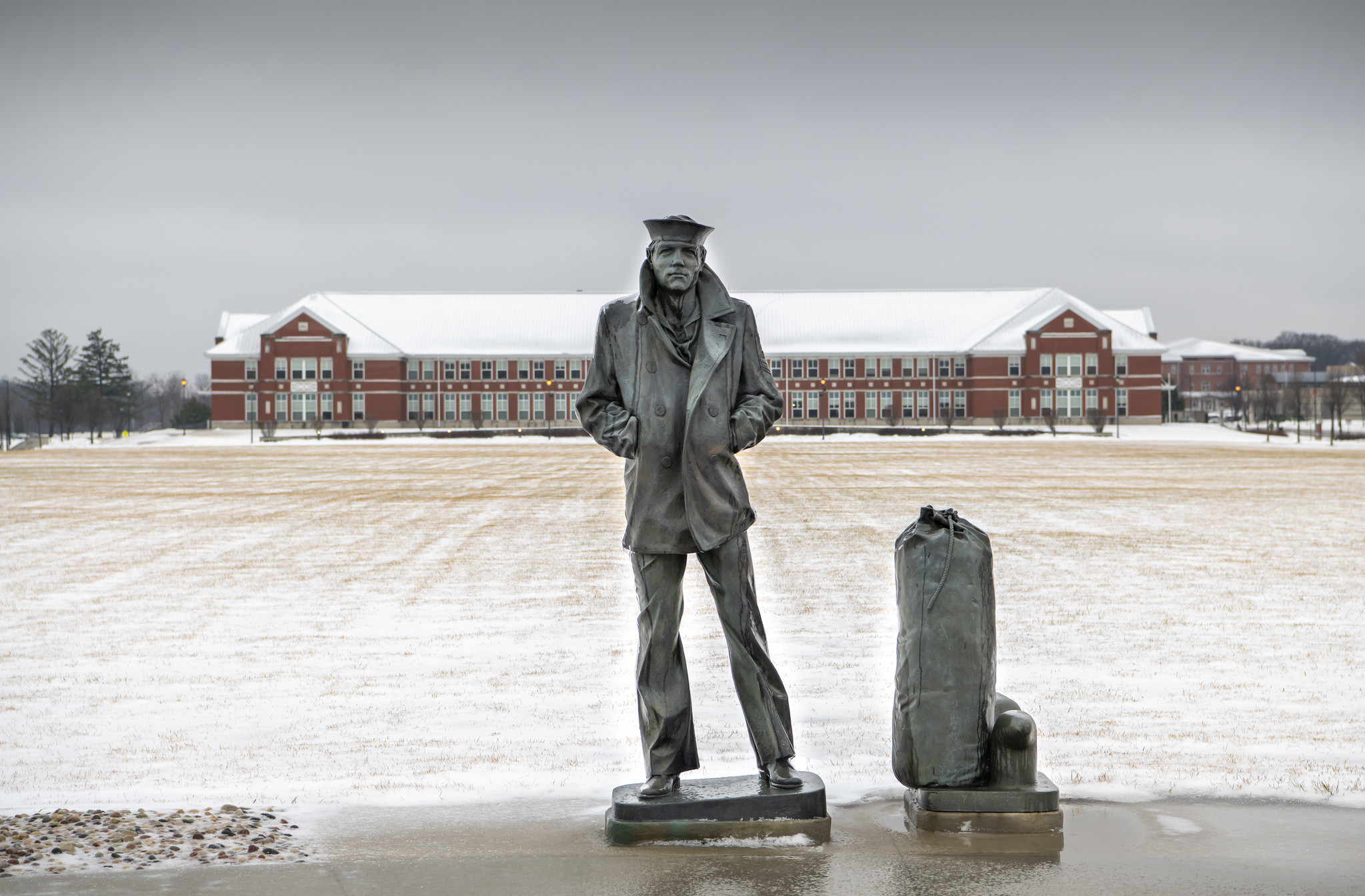 The statue of the Lone Sailor stands on the snow-covered grounds of Recruit Training Command at Great Lakes, Ill., on Dec. 30, 2020. (MC1 Spencer Fling/Navy)