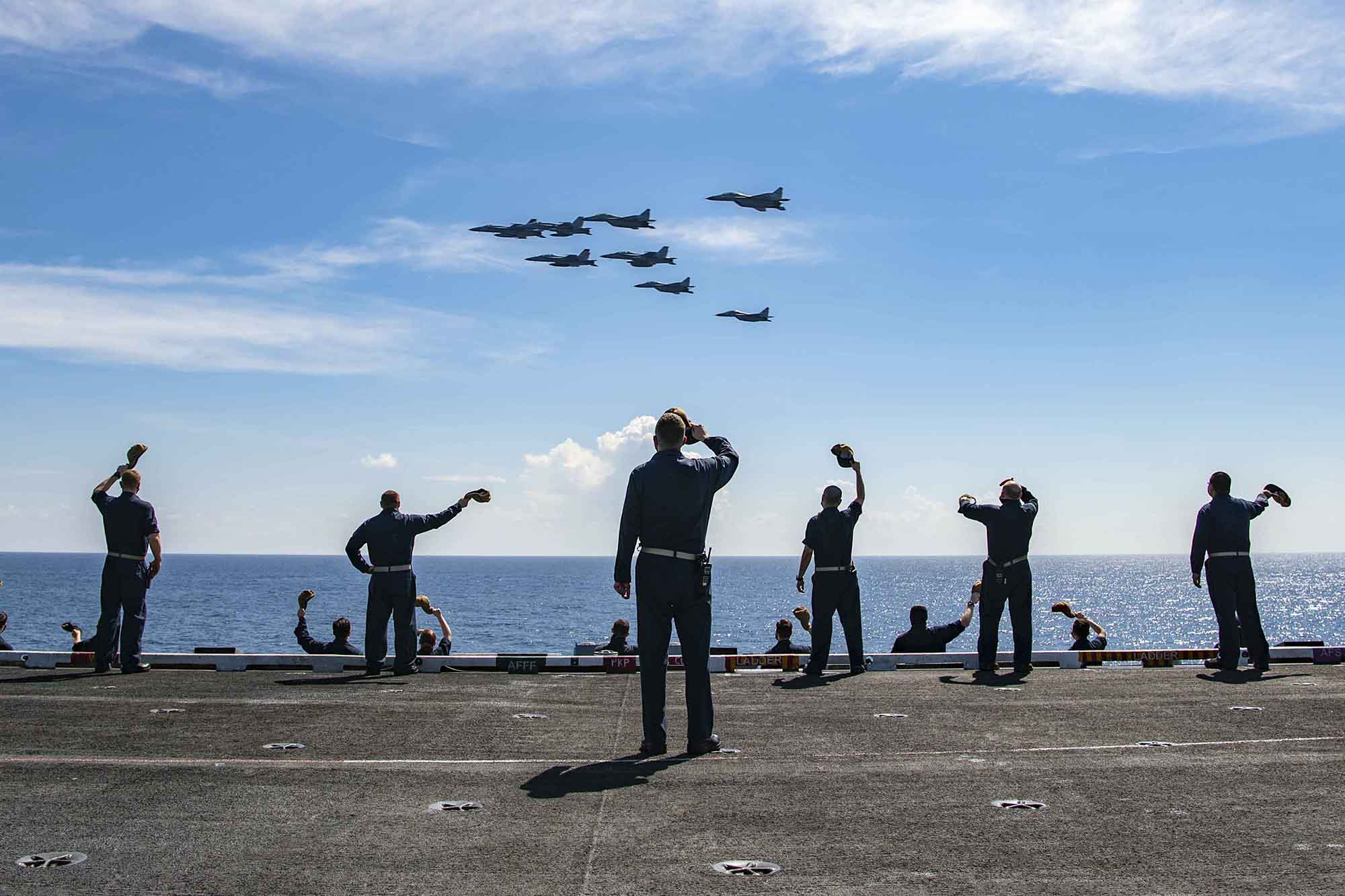 Master Chief David Conduff, command master chief of the aircraft carrier USS Nimitz (CVN 68), waves to four F-18s from the Nimitz and four MiG 29K Fulcrum K from the Indian navy aircraft carrier INS Vikramaditya (R 33) on Nov. 20, 2020, from the flight deck of the Nimitz while participating in Malabar 2020 in the Indian Ocean. (MC3 Charles DeParlier/Navy)