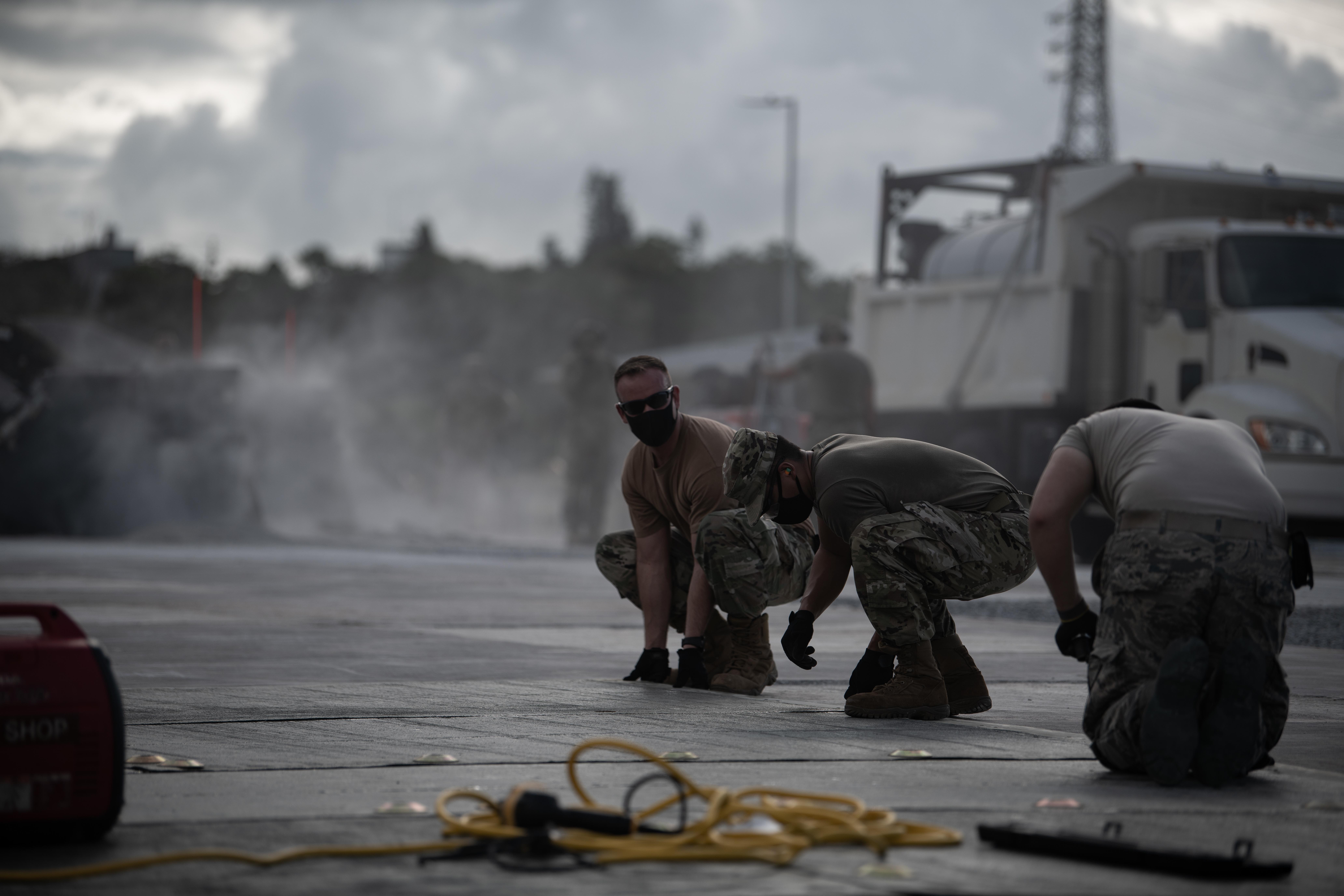 U.S. Air Force Tech. Sgt. William Blevins positions a mat of fiber-reinforced polymer to repair airfield damage during Valiant Shield 2020 at Kadena Air Base, Japan, on Sept. 22, 2020. (Tech. Sgt. Daniel E. Fernandez/U.S. Air Force)