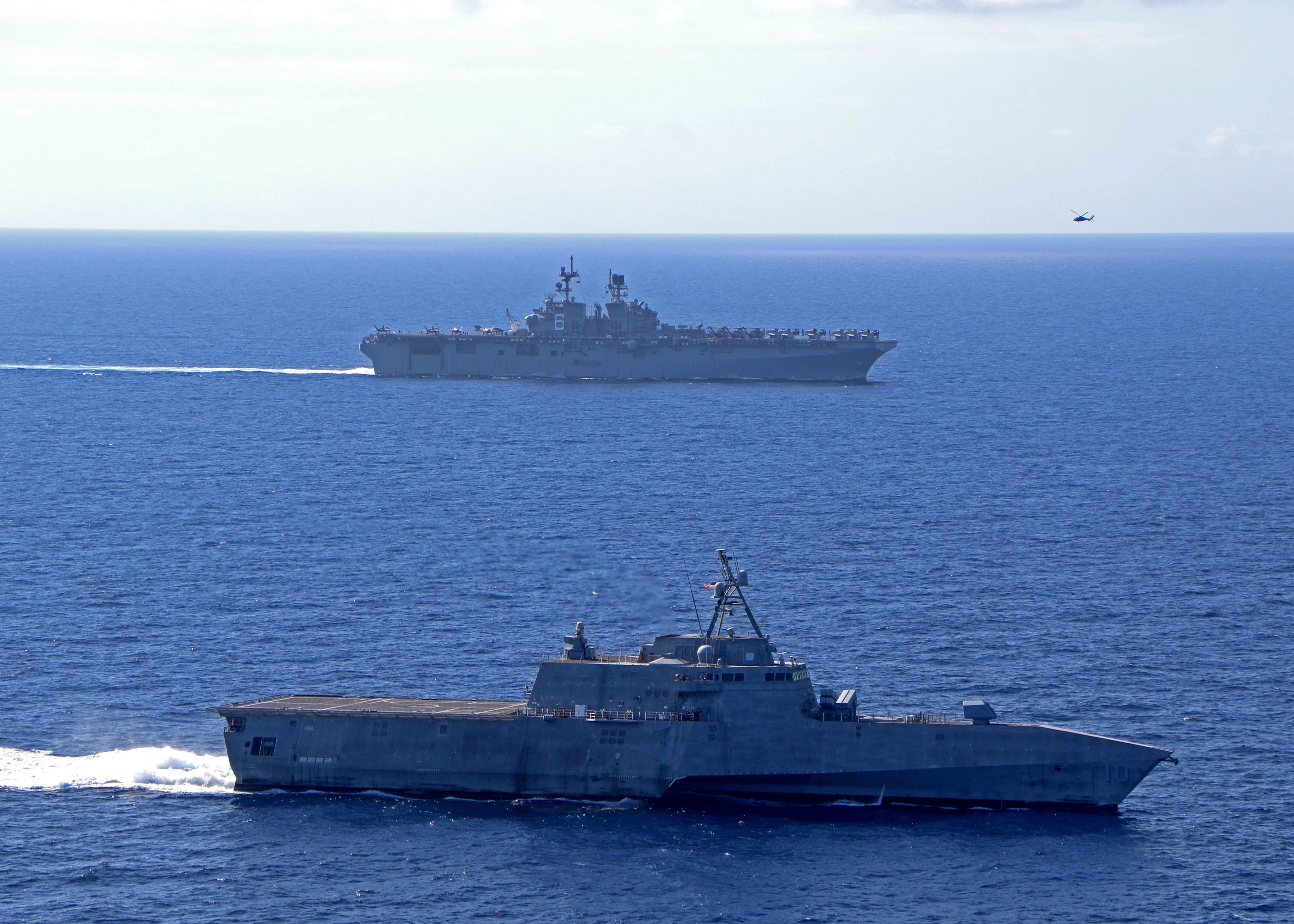 The amphibious assault ship America sails alongside Independence-variant littoral combat ship Gabrielle Giffords on March 13, 2020, in the South China Sea. (U.S. Navy)