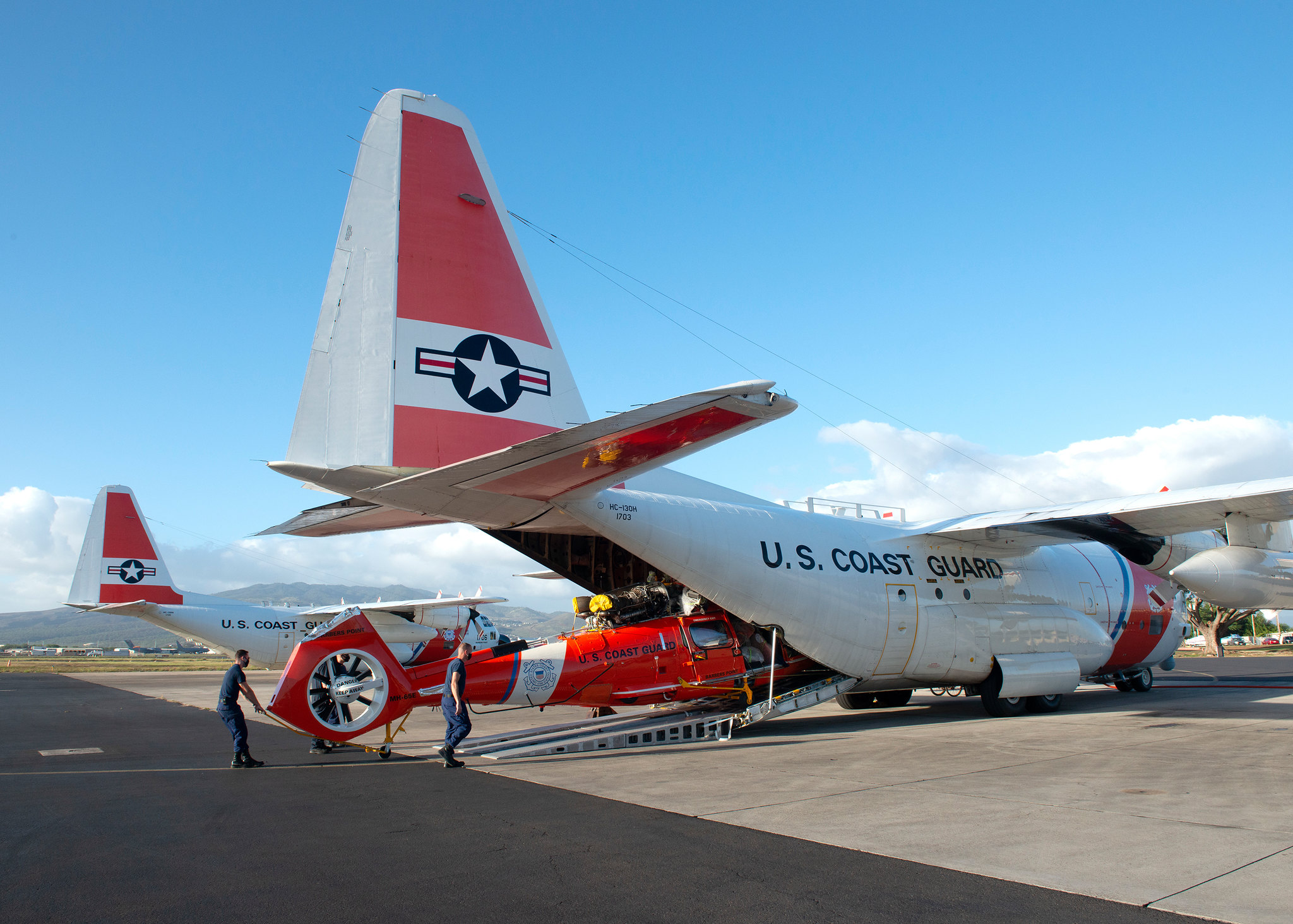 """A Coast Guard Air Station Barbers Point aircrew unloads a MH-65E Dolphin helicopter from a HC-130 Hercules airplane on Oahu, Hawaii, Jan. 28, 2021. The helicopter is a new """"echo"""" model with improvements ranging from enhanced digital weather/surface radar to modernization of the avionics from the previous """"delta"""" model. (Petty Officer 2nd Class Matthew West/Coast Guard)"""