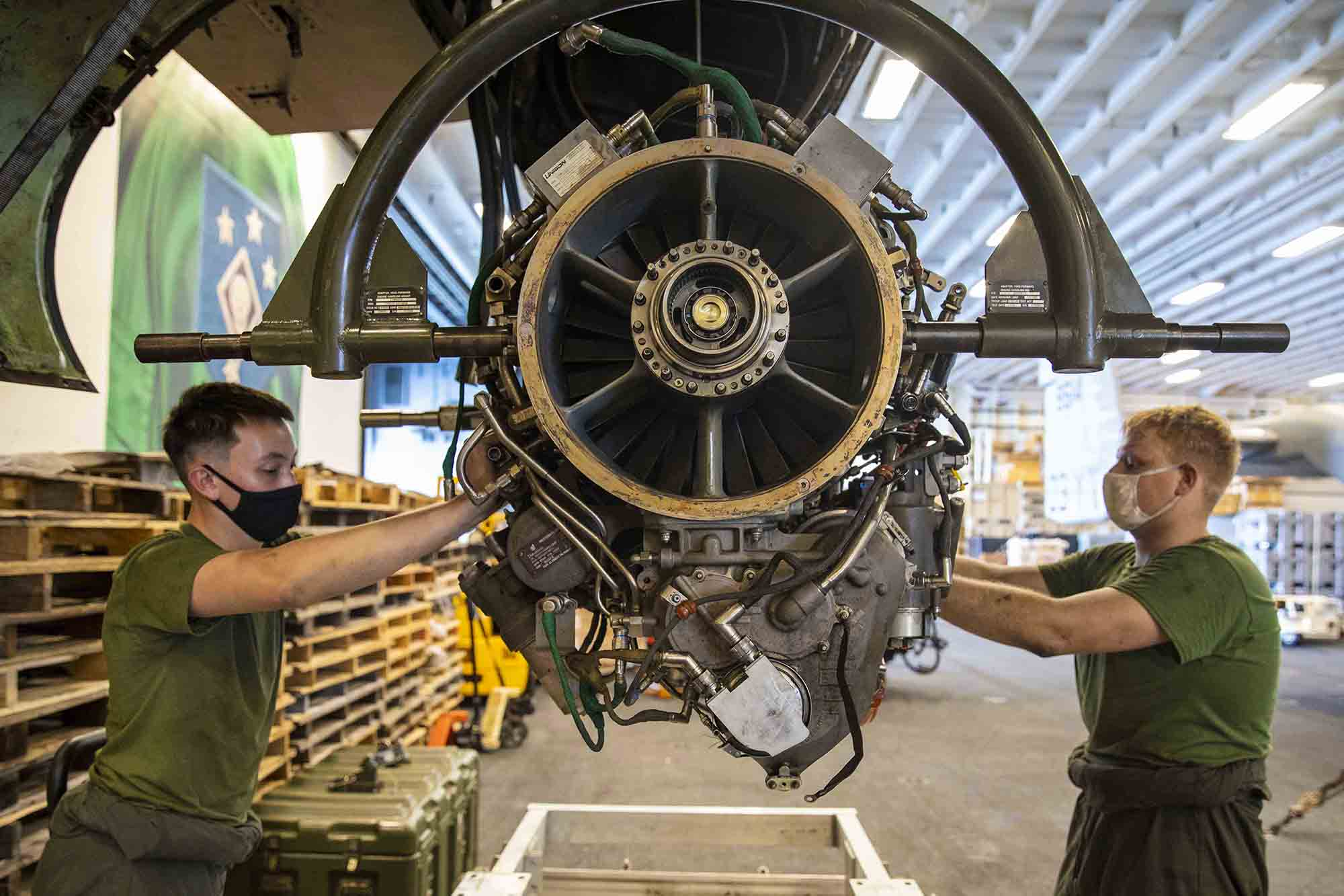 Marine Corps Sgt. William Easter, right, and Lance Cpl. Nathaniel Hinkle remove an engine from an Osprey aboard the amphibious assault ship USS Makin Island (LHD 8) on Jan. 19, 2021, in the Indian Ocean. (MC3 Aaron Sperle/Navy)