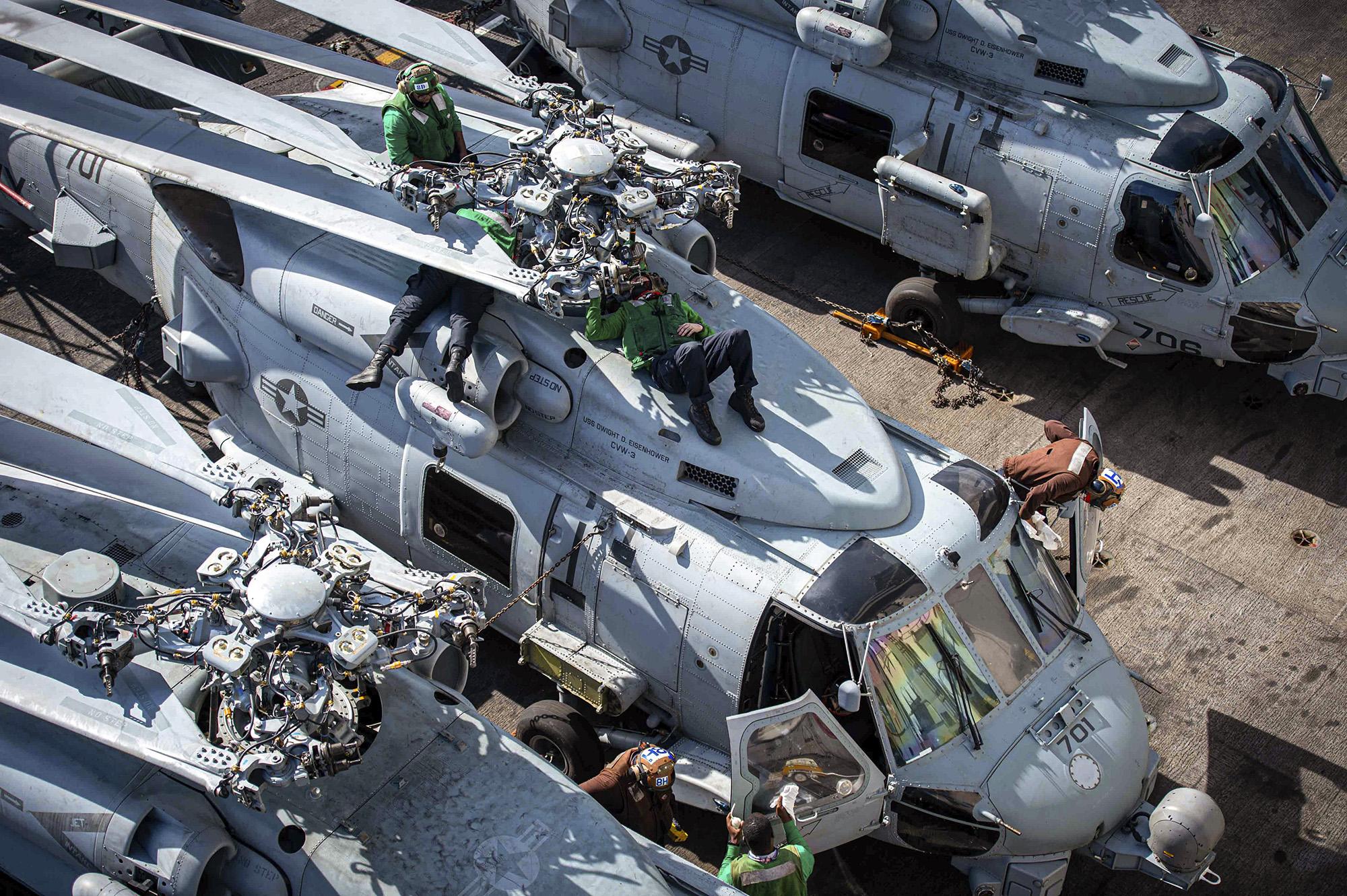Sailors perform maintenance on an MH-60R Sea Hawk on Jan. 27, 2021, on the flight deck aboard the Nimitz-class aircraft carrier USS Dwight D. Eisenhower (CVN 69) in the Atlantic Ocean. (Mass Communication Specialist Seaman Orion Shotton/Navy)