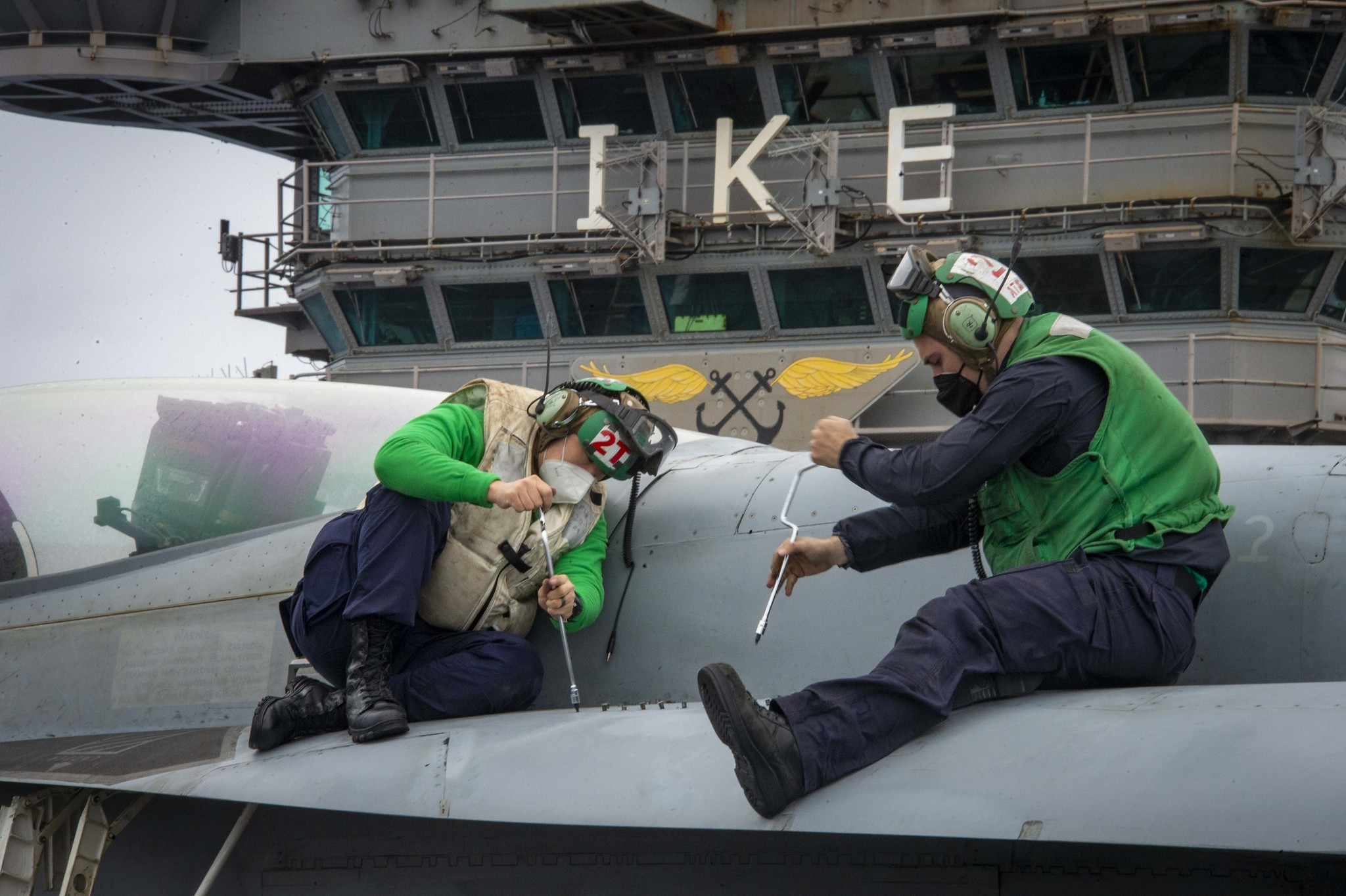 Aviation Electronics Technician 3rd Class Hongyuan Wang, left, and Aviation Electronics Technician 3rd Class Kameron Hair conduct maintenance Feb. 23, 2021, on an F/A-18E Super Hornet on the flight deck aboard the aircraft carrier USS Dwight D. Eisenhower (CVN 69) in the Atlantic Ocean. (MC3 Jairus P. Bailey/Navy)