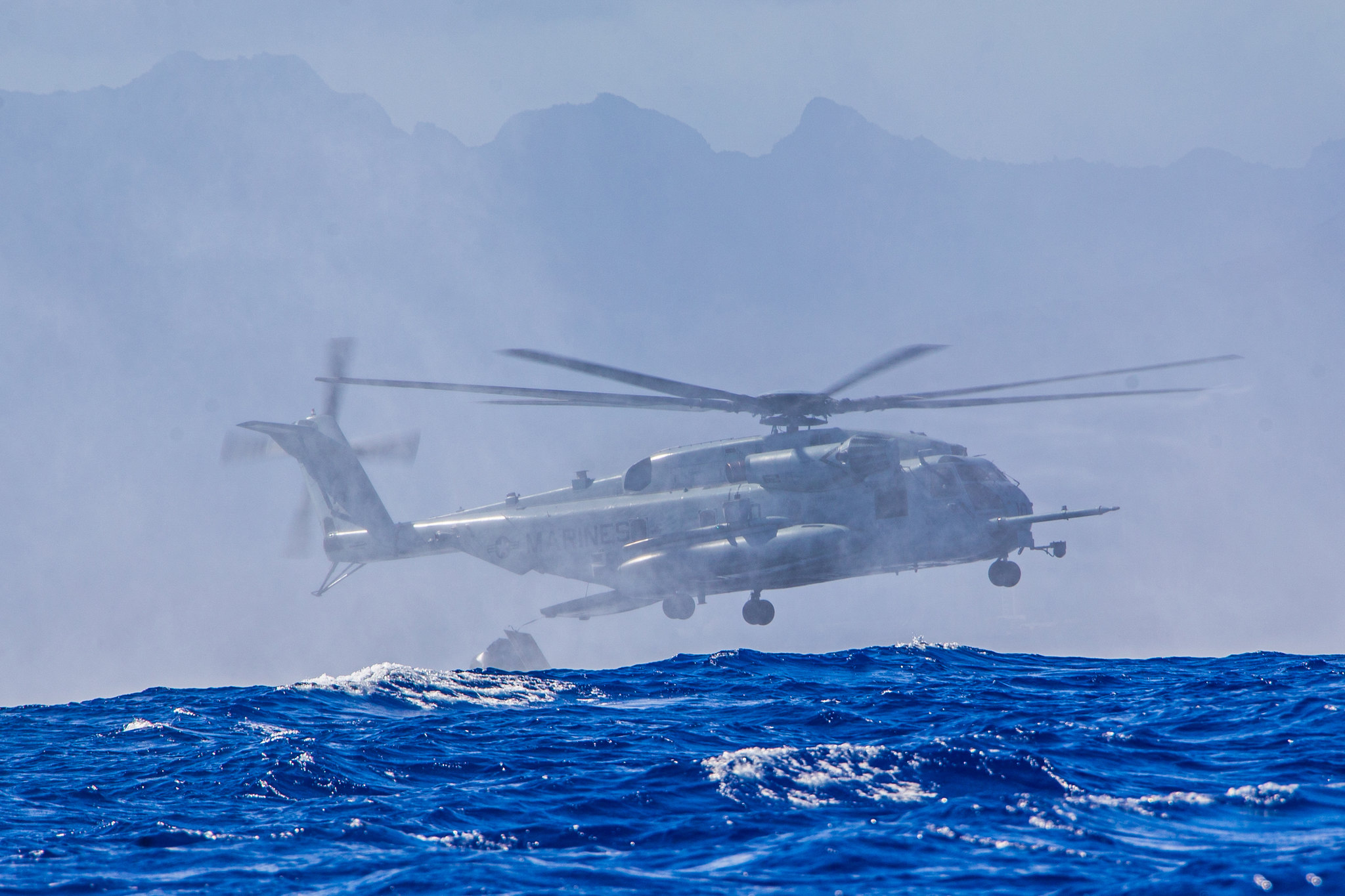 Marines approach the water with a CH-53E Super Stallion helicopter during helicopter casting training with U.S. Navy sailors off the island of Oahu, Hawaii, June 30, 2020. (Lance Cpl. Jacob Wilson/Marine Corps)
