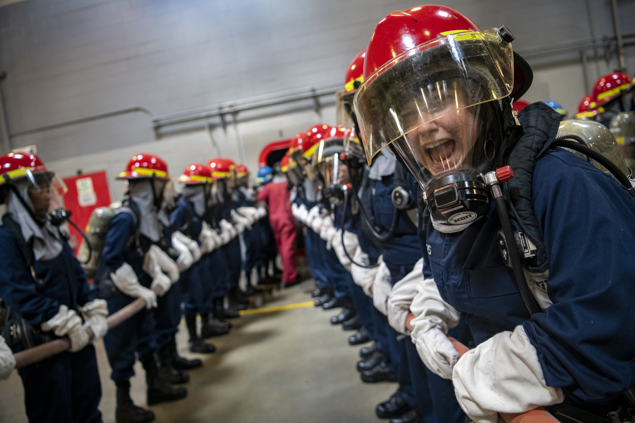Recruits participate in firefighting and damage control training inside the USS Chief Fire Fighter Trainer on July 29, 2020, as part of the hands-on learning at Recruit Training Command at Great Lakes, Ill. (MC1 Camilo Fernan/Navy)