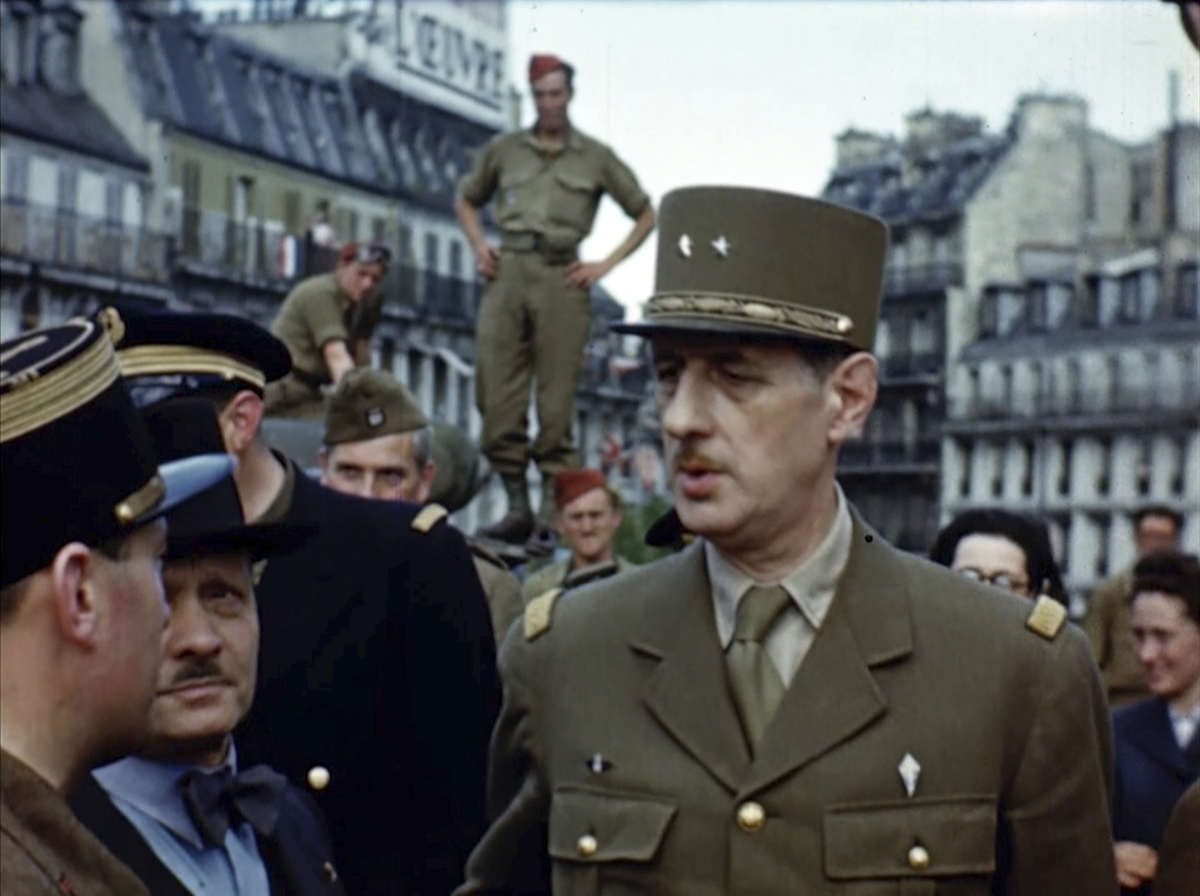 Charles de Gaulle, right, speaks to a French citizen, center, and another French officer after the liberation of Paris in 1944 during World War II. Seventy-five years later, surprising color images of the D-Day invasion and aftermath bring an immediacy to wartime memories. They were filmed by Hollywood director George Stevens and rediscovered years after his death. (War Footage From the George Stevens Collection at the Library of Congress via AP)