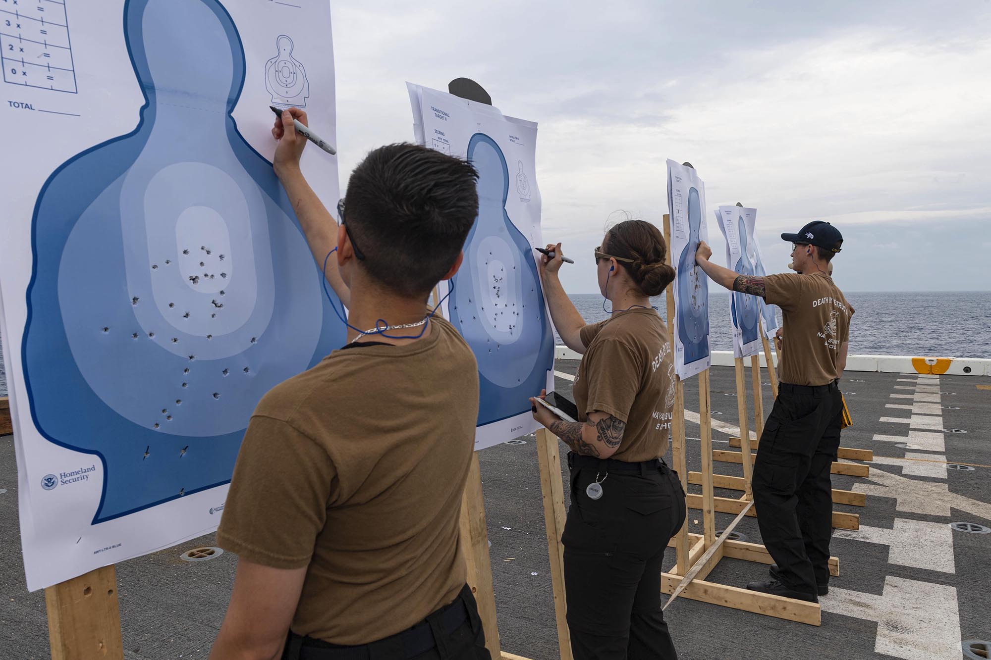 Sailors aboard USS New Orleans (LPD 18) serving as weapons instructors score targets May 30, 2021, following a qualifying gun shoot for sailors assigned to the ship in the East China Sea. (MC2 Desmond Parks/Navy)