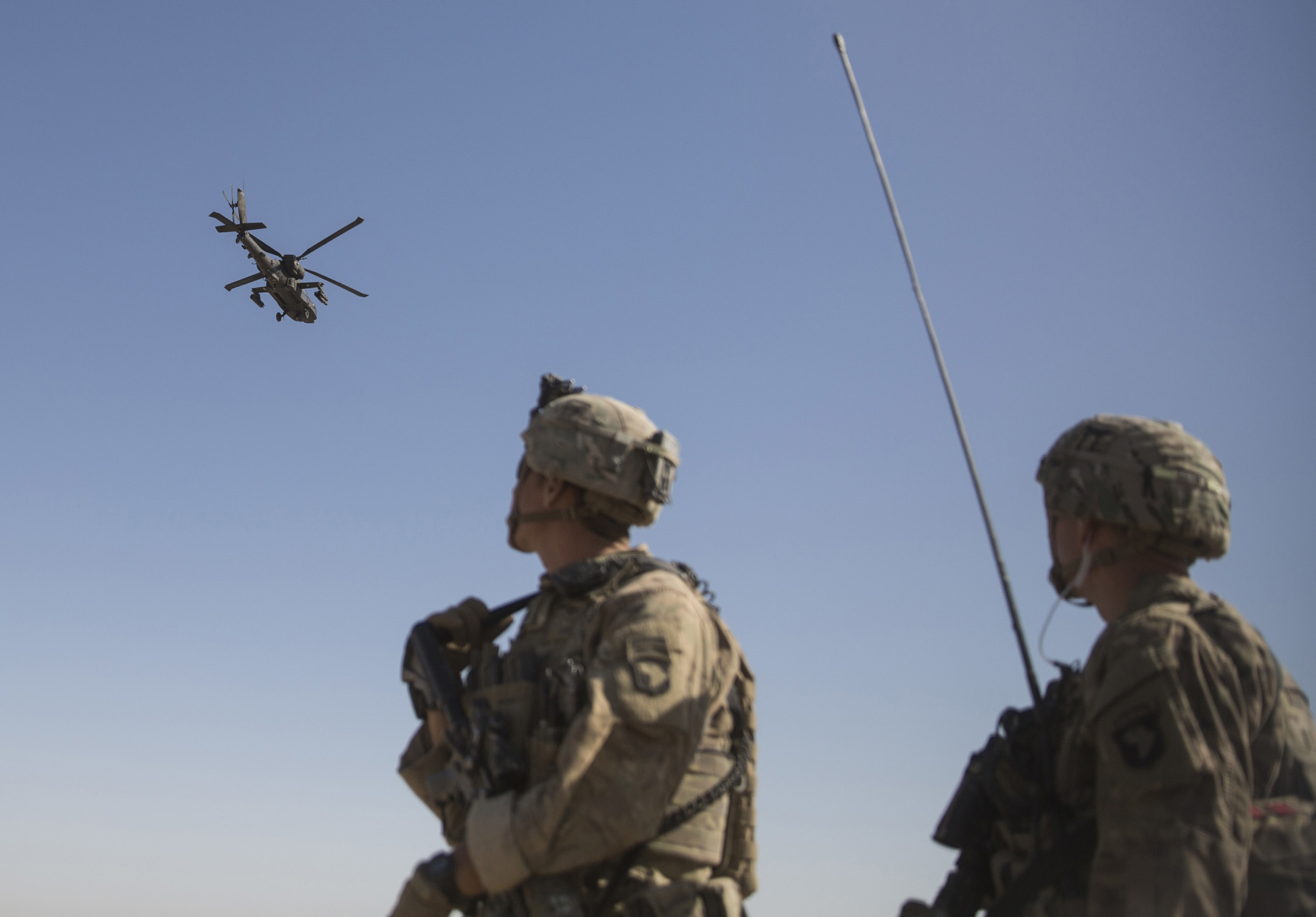 An AH-64 Apache attack helicopter provides security from above while CH-47 Chinooks drop off supplies to U.S. soldiers on June 10, 2017, at Bost Airfield, Afghanistan. (Sgt. Justin T. Updegraff/U.S. Marine Corps via AP)