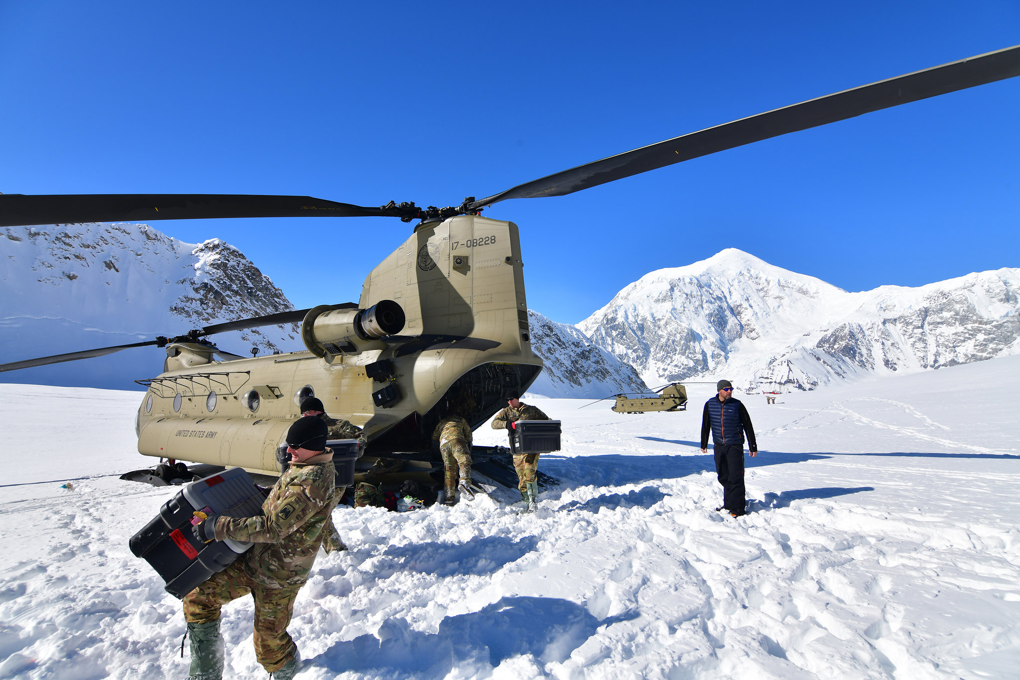 Soldiers from B Company, 1st Battalion, 52nd Aviation Regiment unload equipment and supplies from a pair of CH-47F Chinook helicopters on Kahiltna Glacier, April 22, 2021. Aviators from the unit, also known as the Sugar Bears, traveled from Fort Wainwright to help the National Park Service get the necessary equipment and supplies in place for the base camp at the 7,200-foot level of Kahiltna Glacier for the 2021 climbing season on Denali, the tallest mountain in North America. (John Pennell/Army)