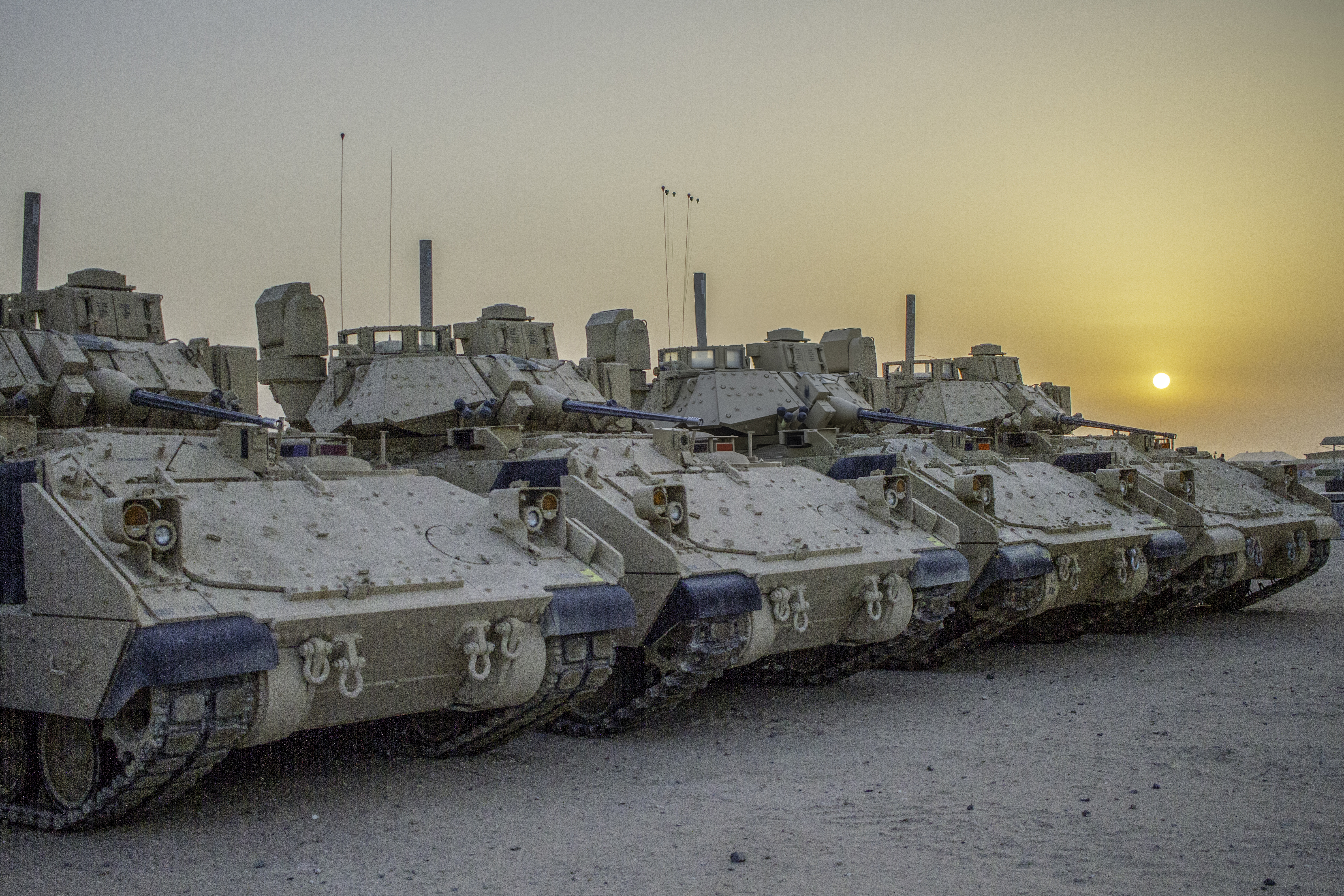 Four M2A3 Bradley Infantry Fighting Vehicles are illuminated in 2018 by the rising sun in a motor pool located at Camp Buehring, Kuwait. (Spc. Jovi Prevot/U.S. Army National Guard photo illustration)