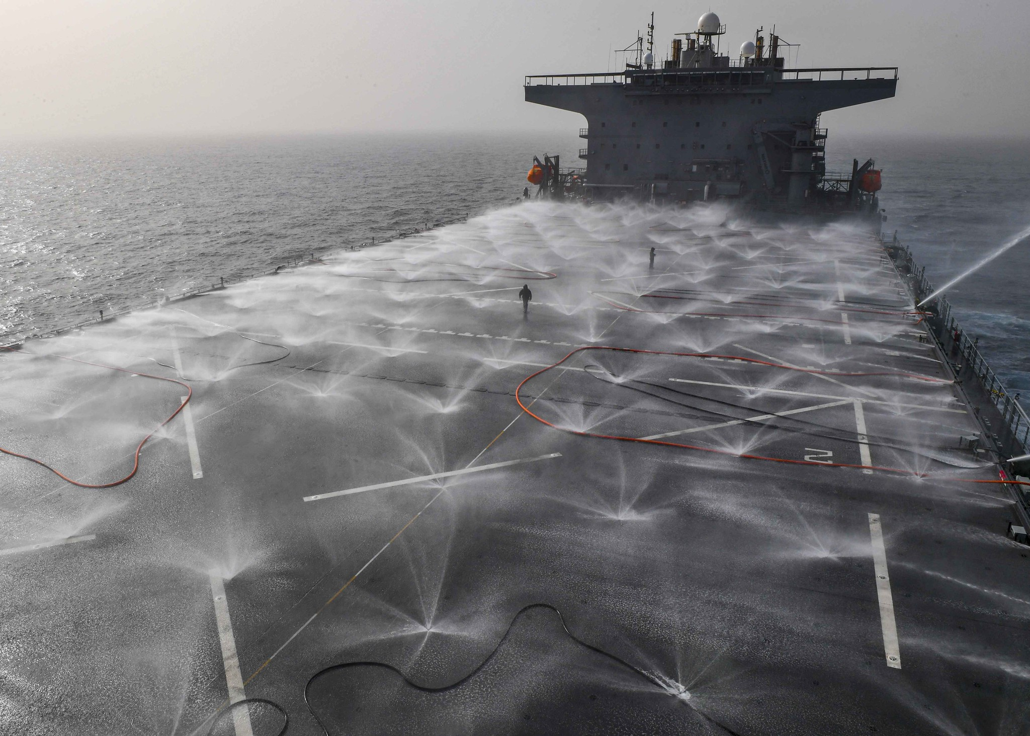"""Sailors from the air department check the functionality of the flight deck sprinkler system on board the expeditionary sea base USS Hershel """"Woody"""" Williams (ESB 4) in the Atlantic Ocean, March 13, 2021. (MC2 Eric Coffer/Navy)"""