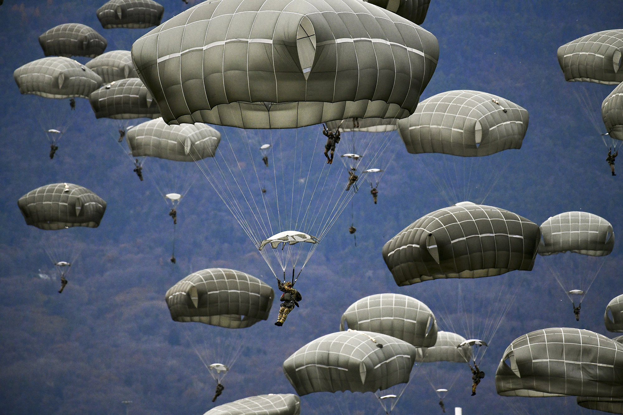 U.S. Army and Italian Army paratroopers conduct airborne operations after exiting a U.S. Air Force C-130 Hercules aircraft at Juliet Drop Zone, Pordenone, Italy, Dec. 10, 2020. (Paolo Bovo/Army)